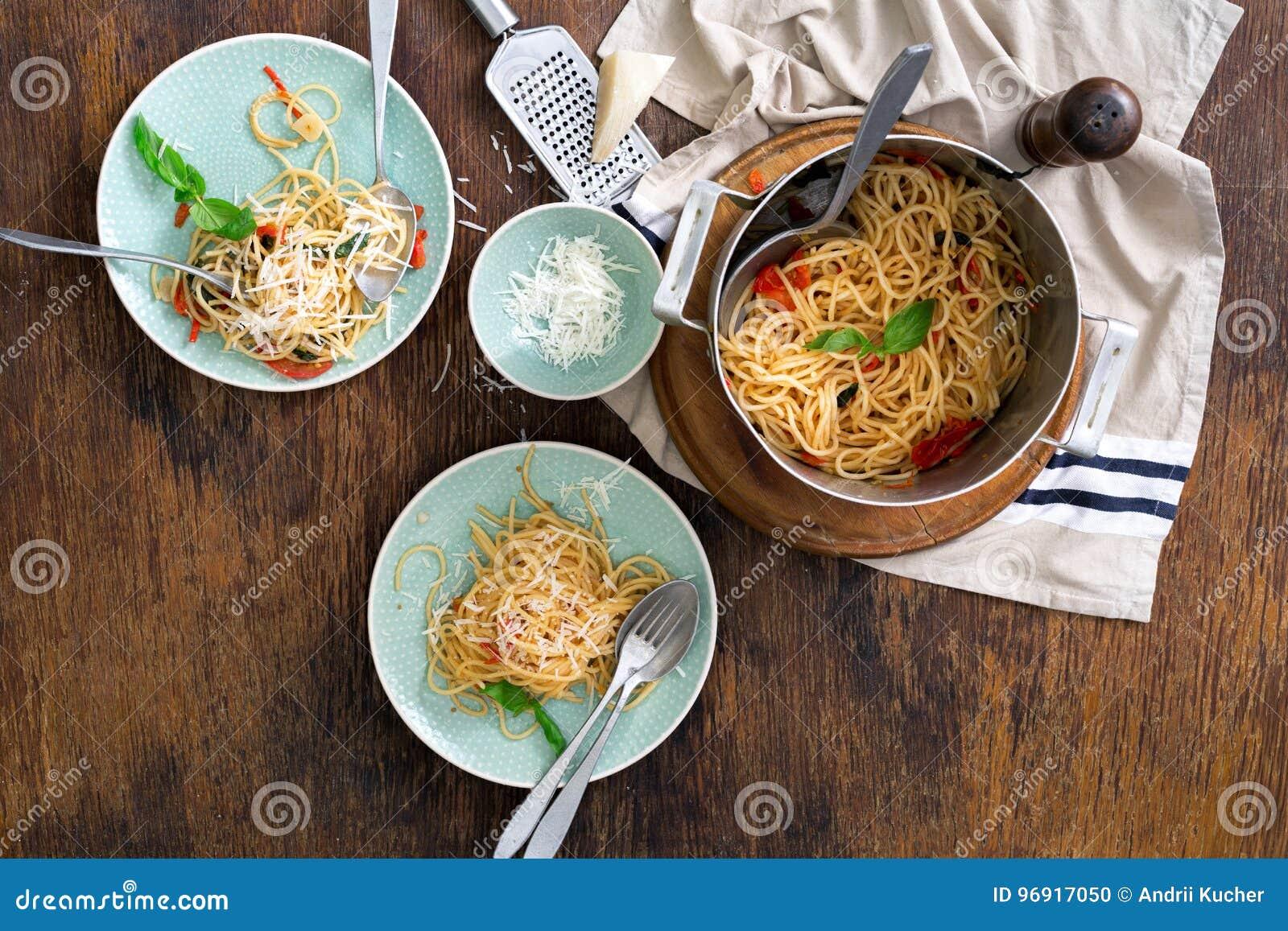 Pastas italianas clásicas con los tomates en una tabla de madera