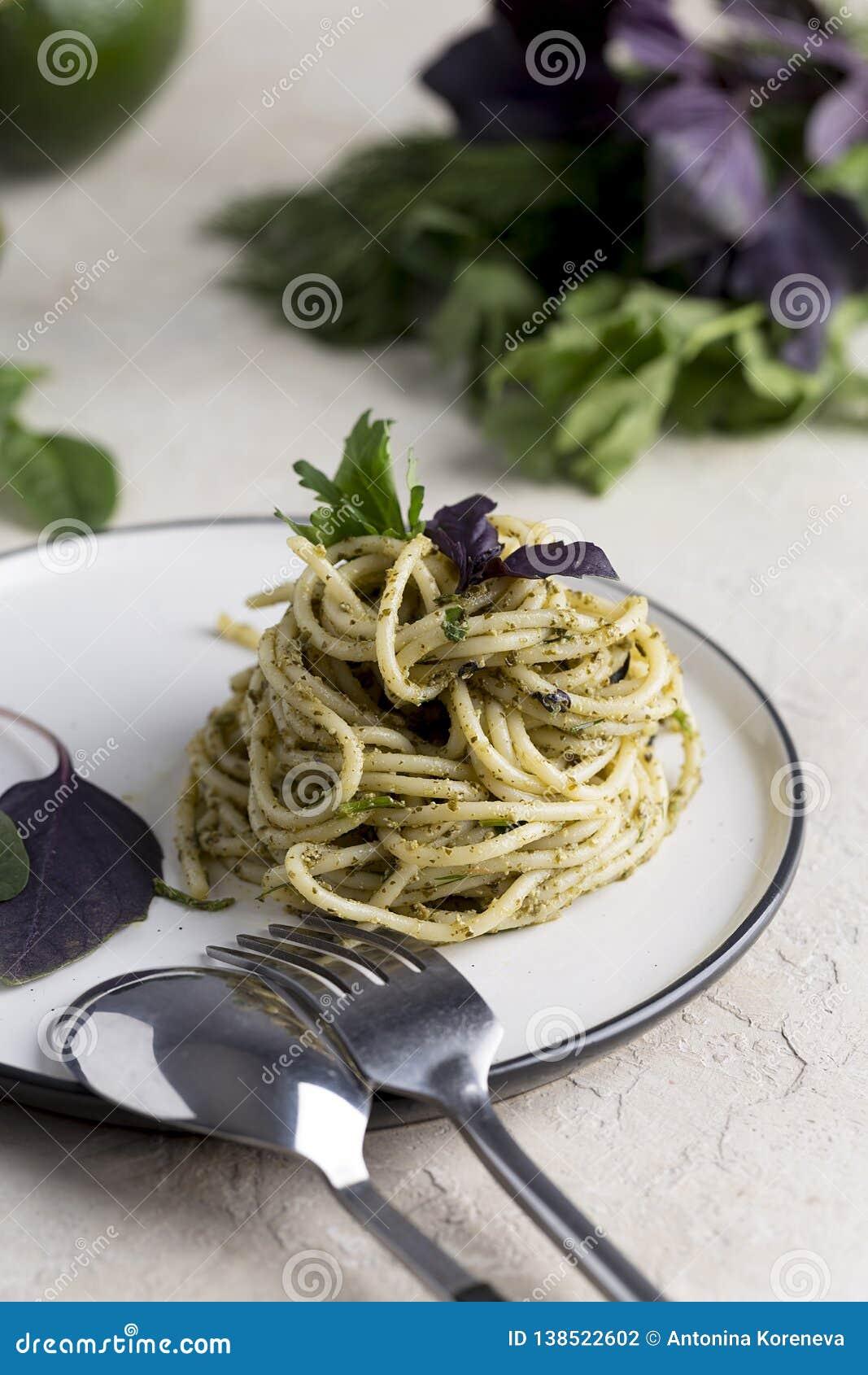 Pastas italianas con pesto de la albahaca en la placa blanca en el fondo ligero