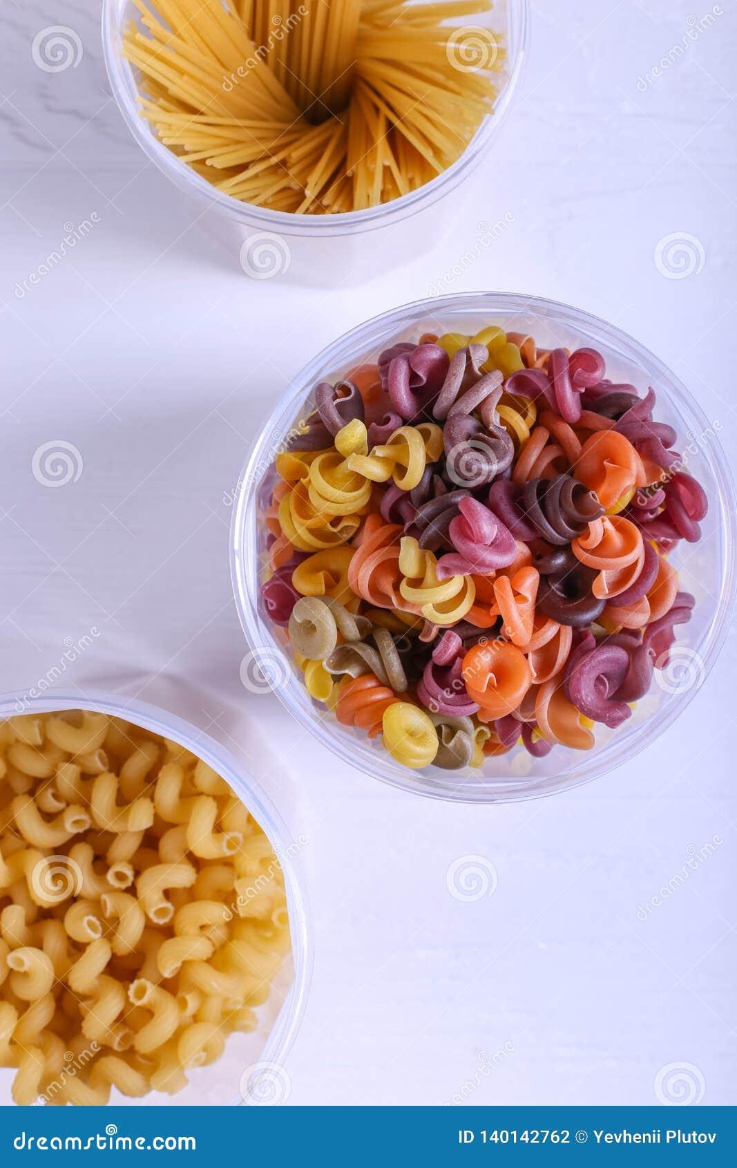 Pastas multicoloras con la adición del tinte vegetal natural En un tarro en una tabla blanca Visión superior, espacio de la copia