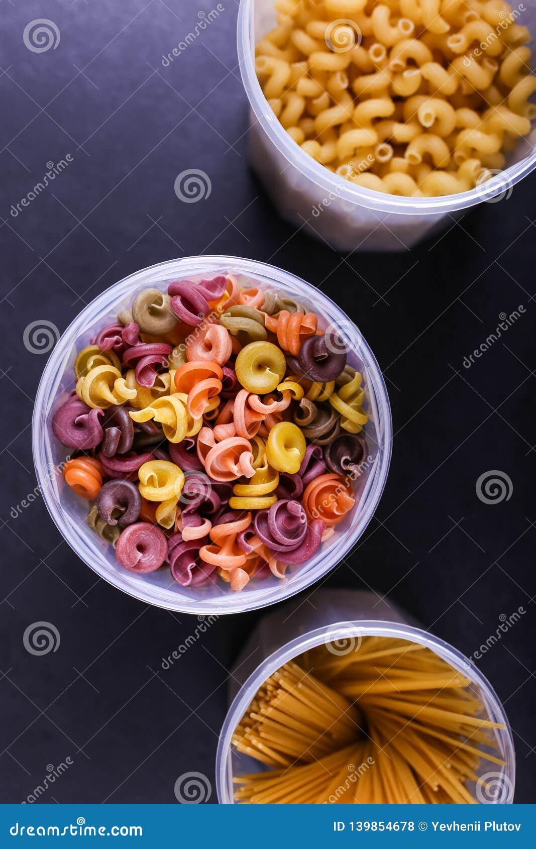 Pastas multicoloras con la adición del tinte vegetal natural En un tarro en una tabla concreta negra Visión superior, espacio de