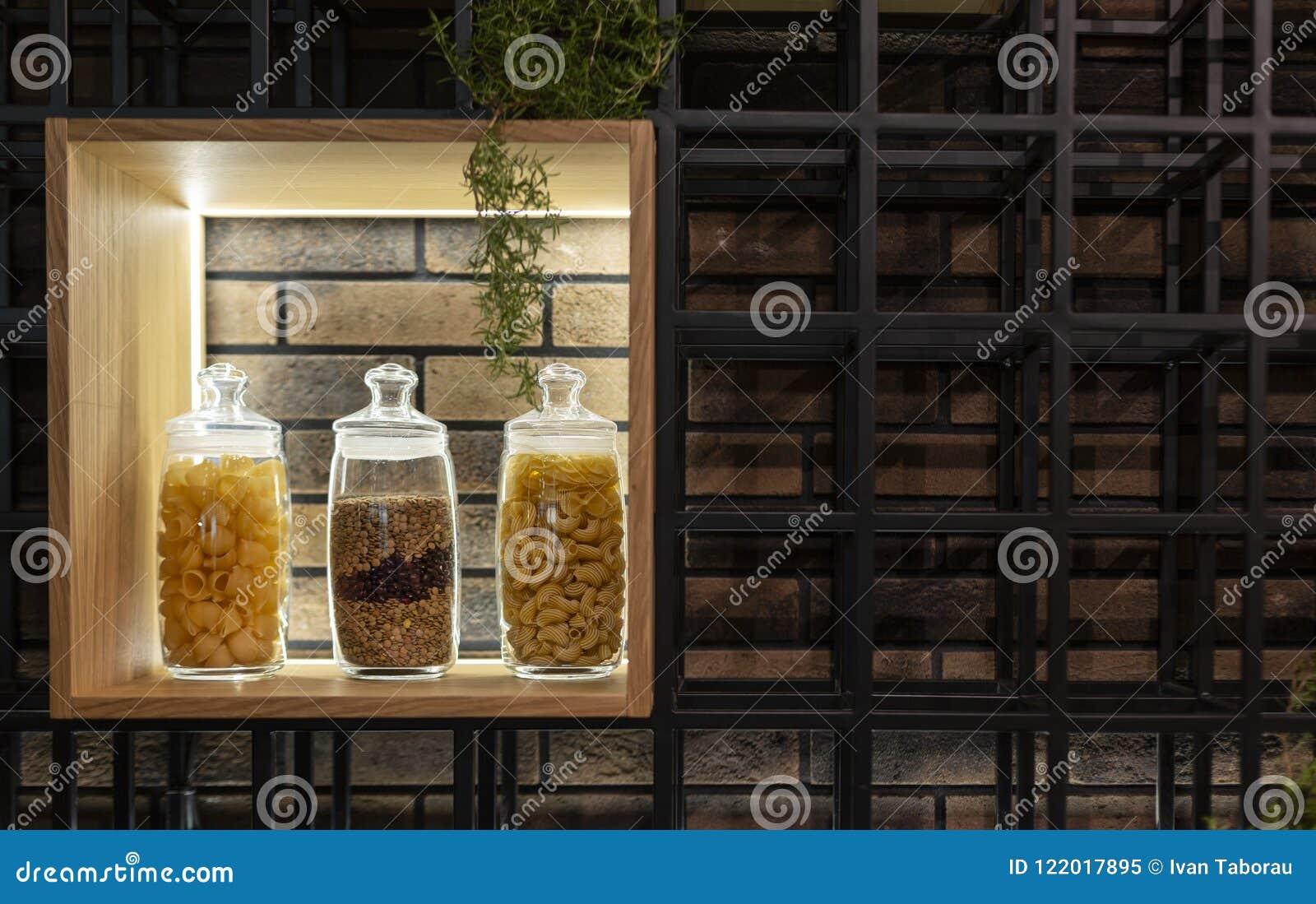 Pastas y espaguetis en un estante en un tarro de cristal en un interior moderno
