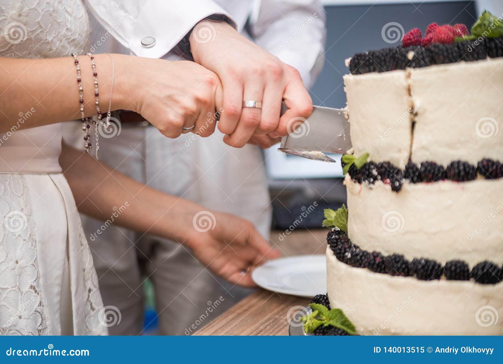 Pastel de bodas con las bayas en la tabla de madera La novia y el novio cortaron la torta dulce en banquete en restaurante
