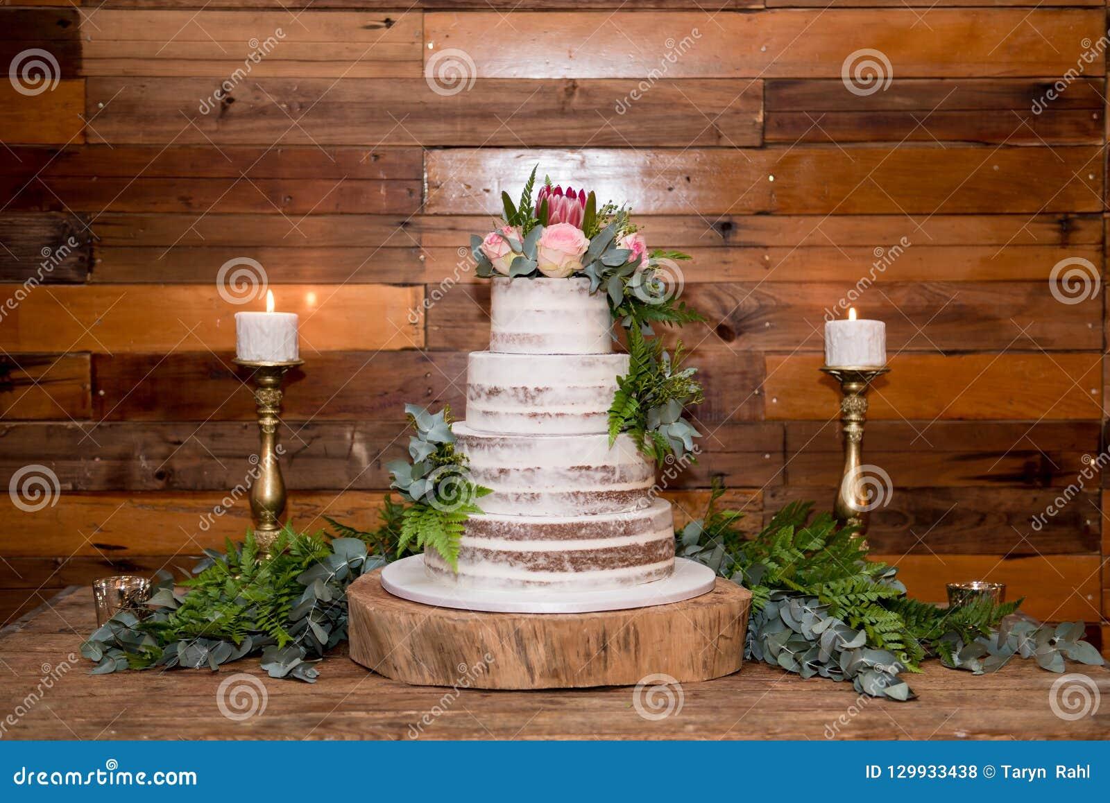 Pastel de bodas con las flores y las velas