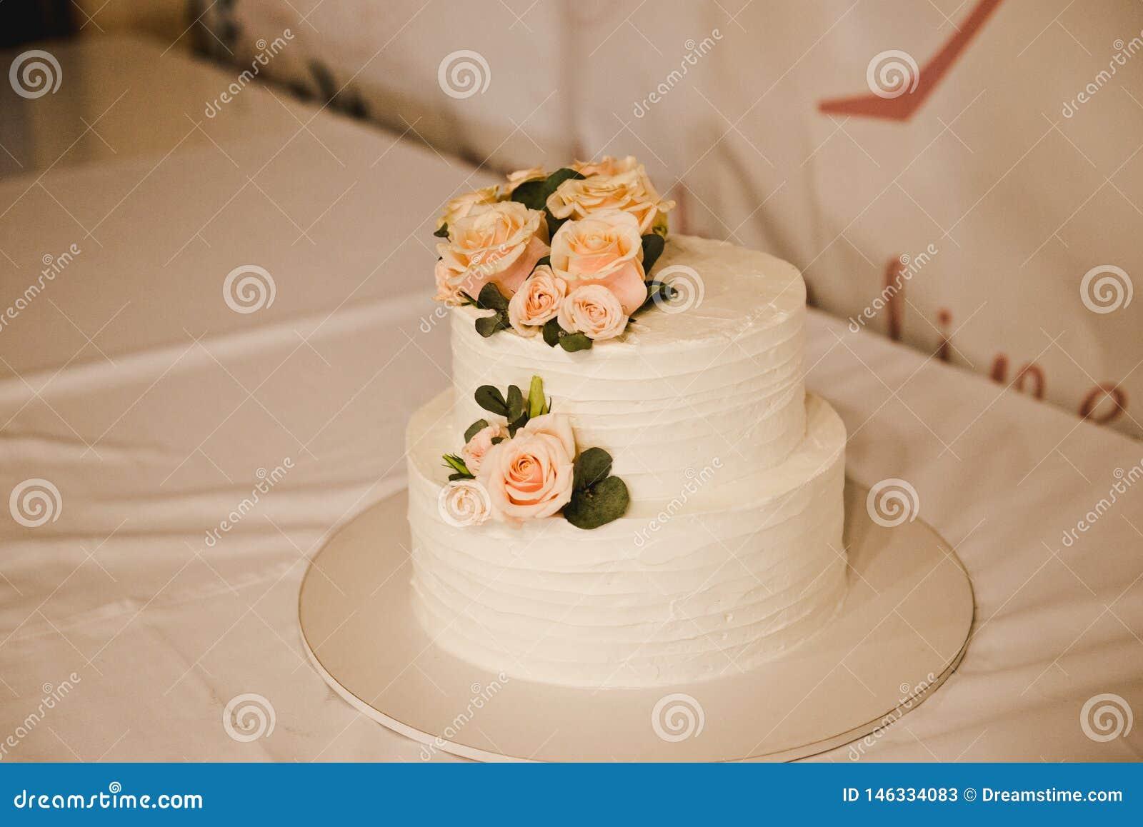 Pastel de bodas festivo con las flores, flores rosado-anaranjadas, litera, hermosa