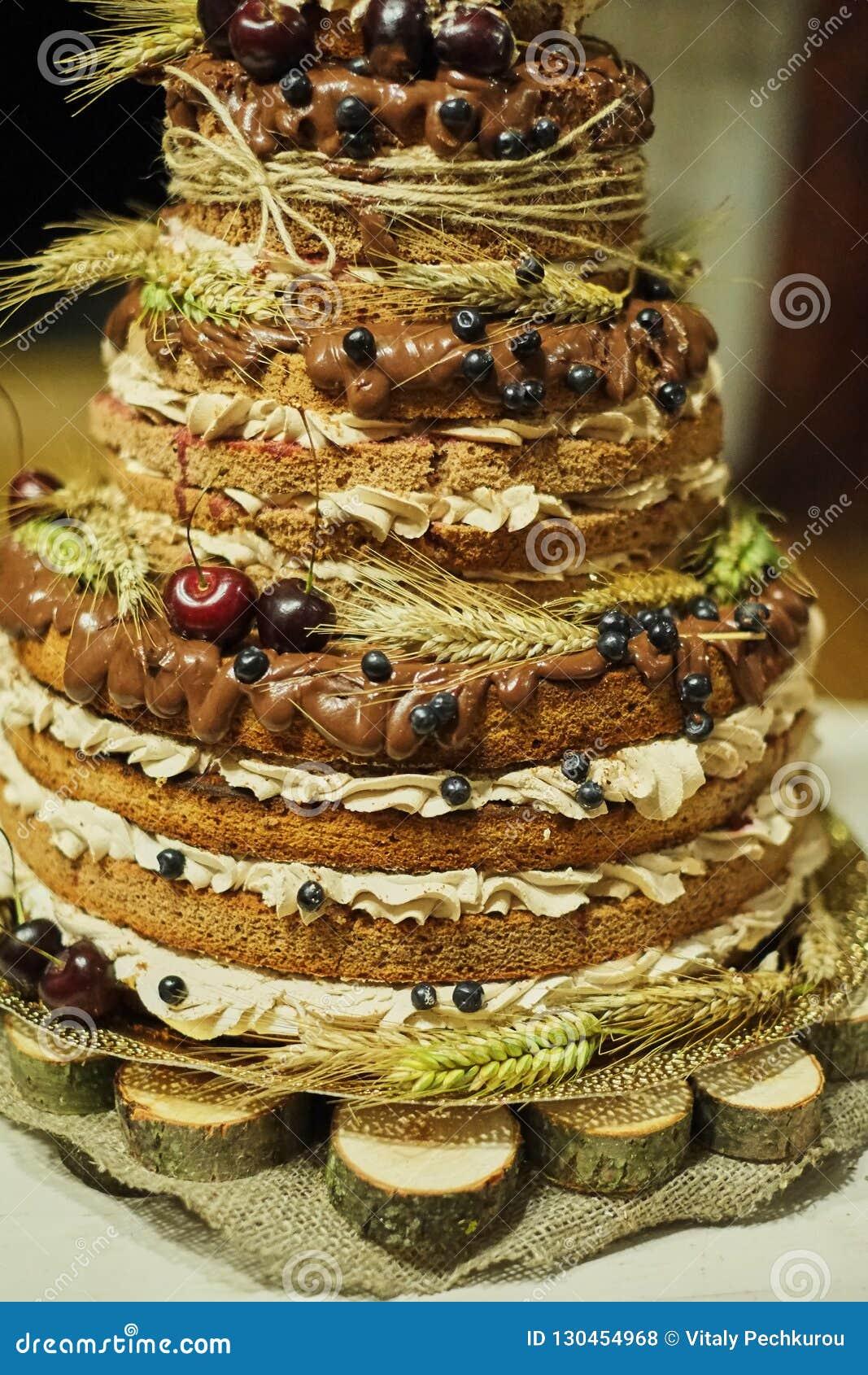 Pastel de bodas multicolor de la galleta de la fruta en un soporte grande hecho de la madera pastel de bodas con gradas en un fon