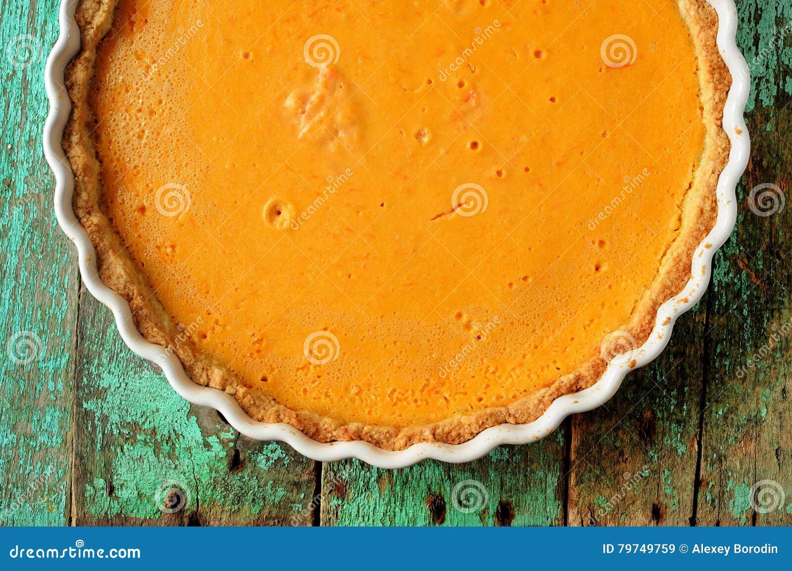 Pastel de calabaza hecho en casa anaranjado brillante redondo fresco en d que cuece blanca