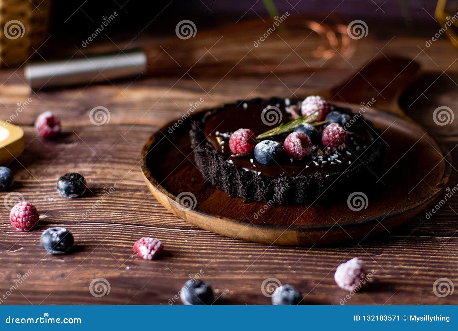 Pastel de queso agrio del chocolate con las bayas frescas Postre delicioso