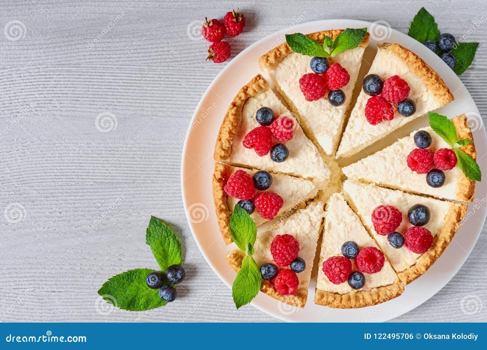 Pastel de queso cortado con las bayas frescas en la placa blanca - postre orgánico sano Pastel de queso clásico de Nueva York