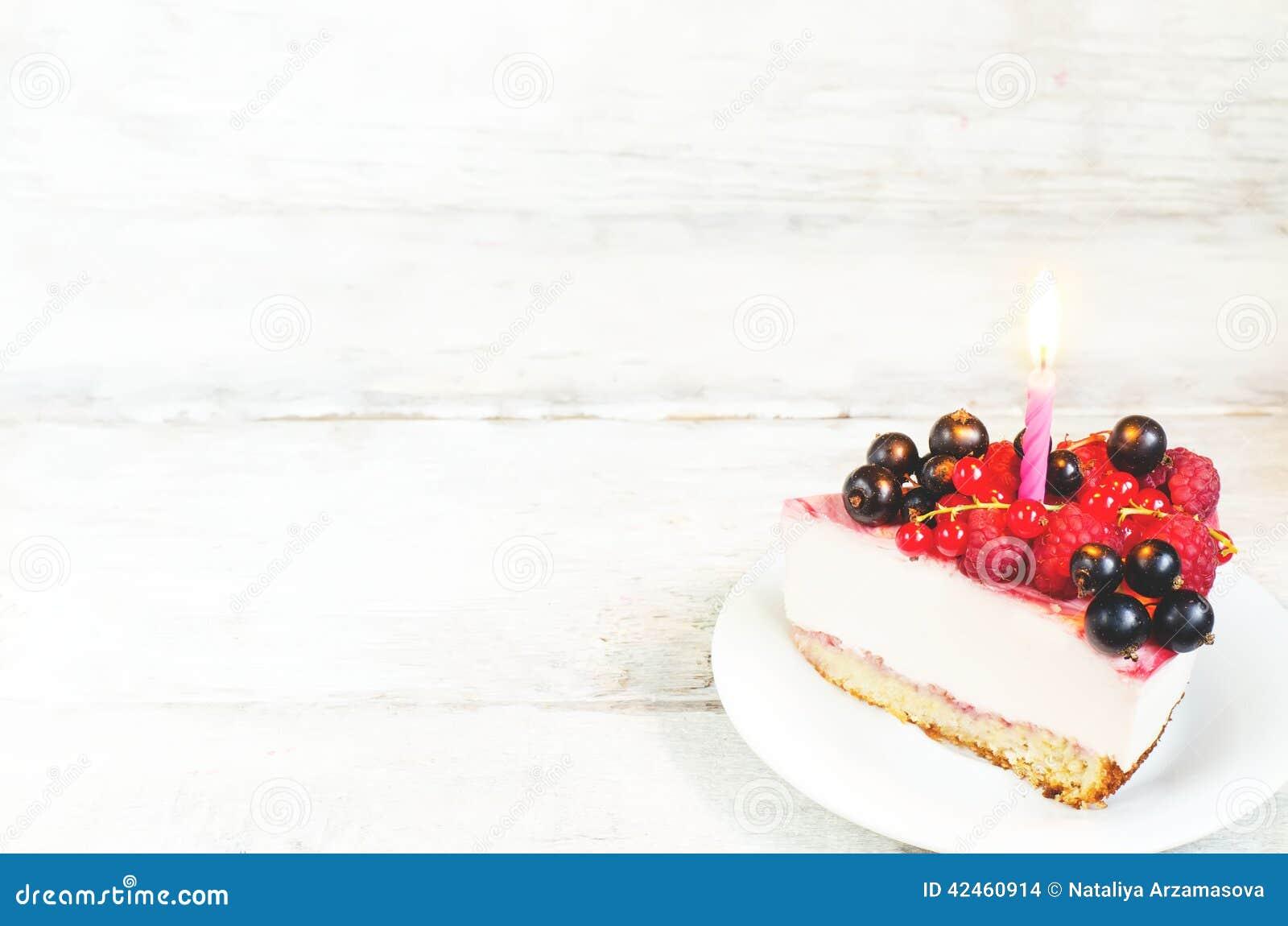 Pastel de queso del cumpleaños con el curr de la vela, de las frambuesas, rojo y negro