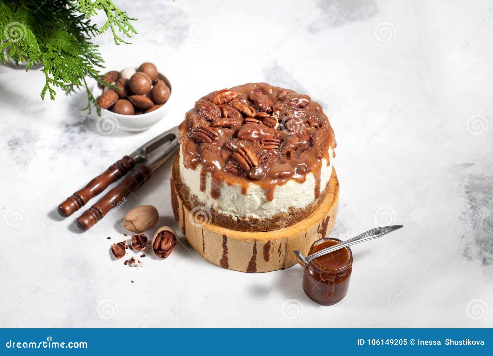 Pastel de queso de la Navidad con las pacanas y la salsa del caramelo