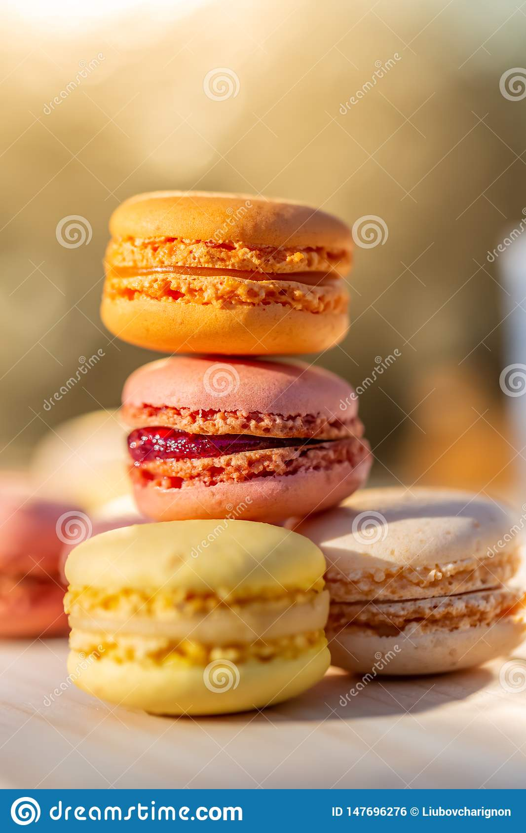 Pasteles franceses coloreados airosos dulces deliciosos Macarons de los dulces por la tarde del verano en una huerta Fondo enmasc