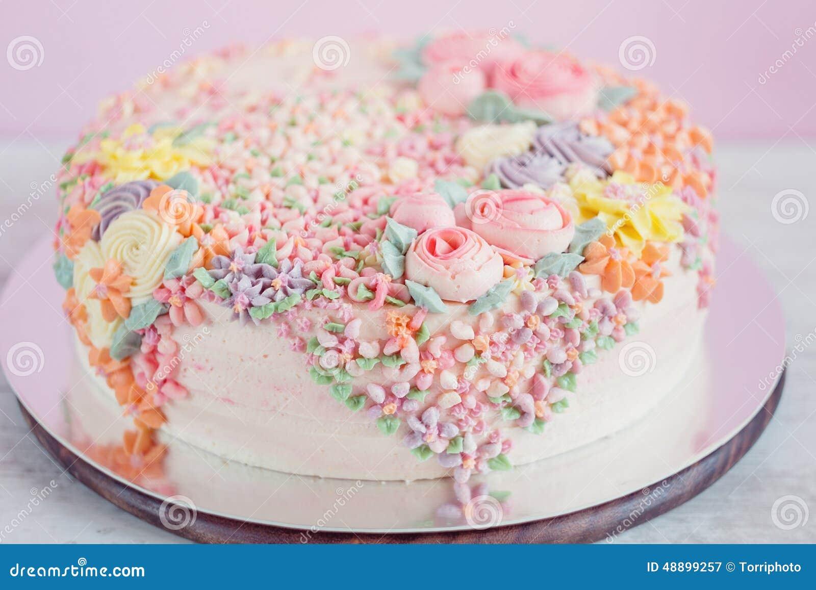 Pastelkleur roze die cake met roombloemen wordt verfraaid stock ...
