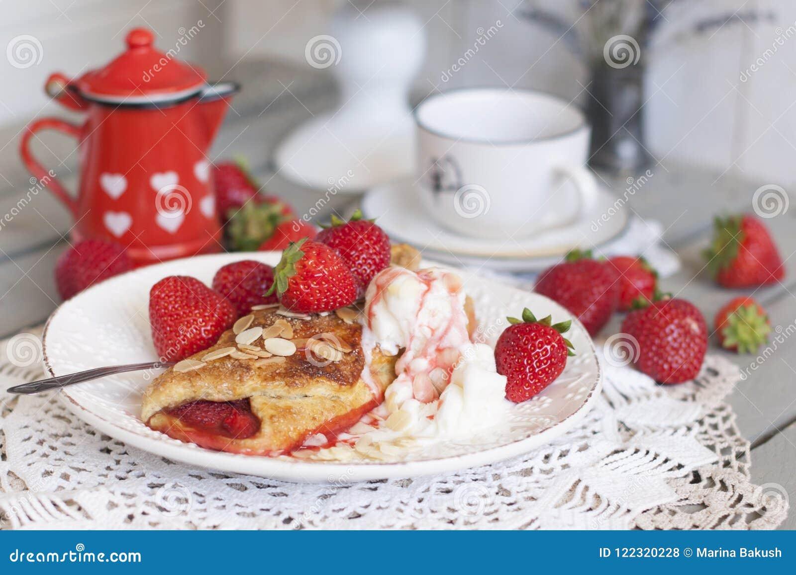 Pasticcerie casalinghe dolci per la prima colazione con il materiale da otturazione della fragola ed il gelato tazza di caffè che