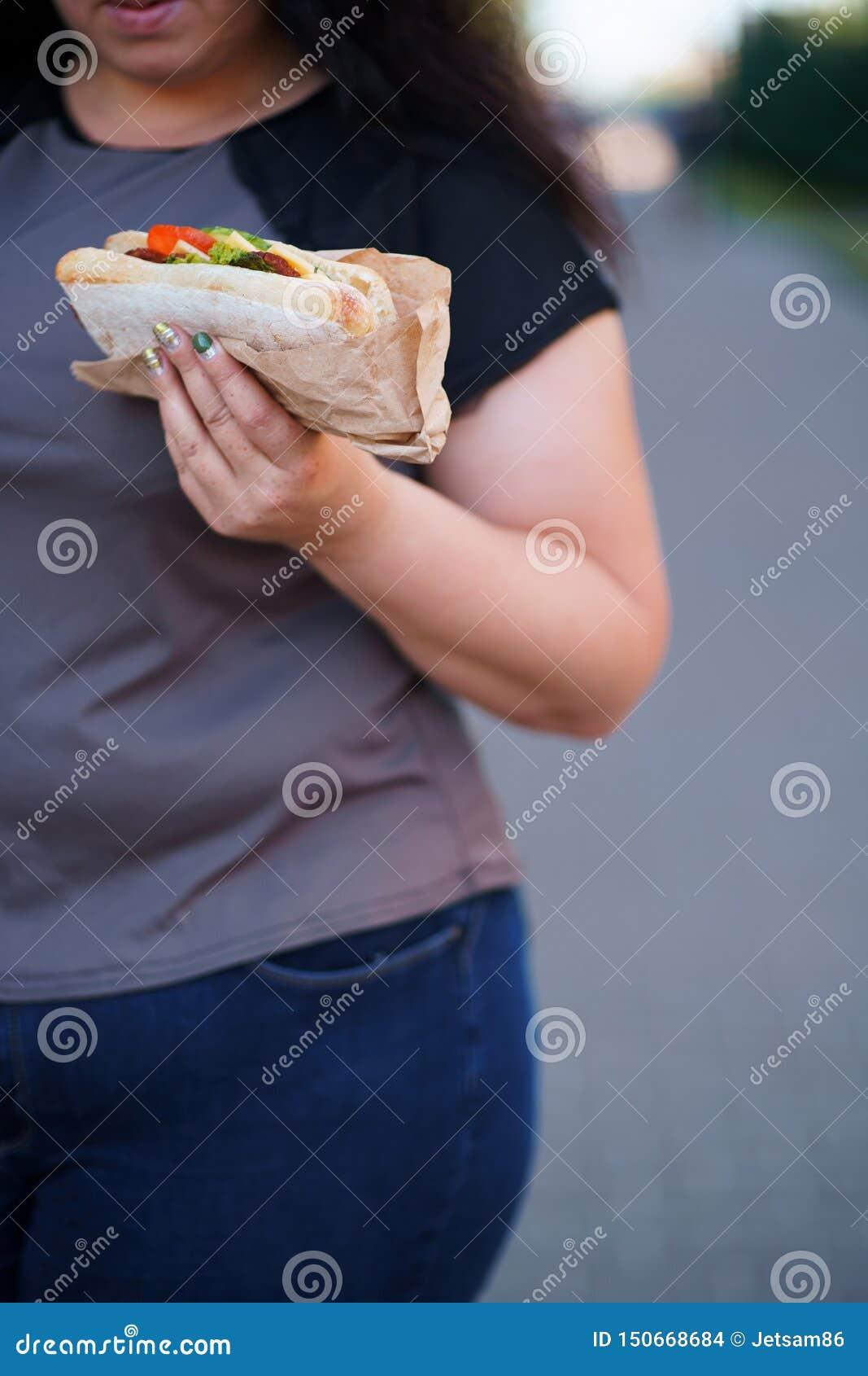 Pasto rapido di peso eccessivo di cibo della donna che cammina all aperto