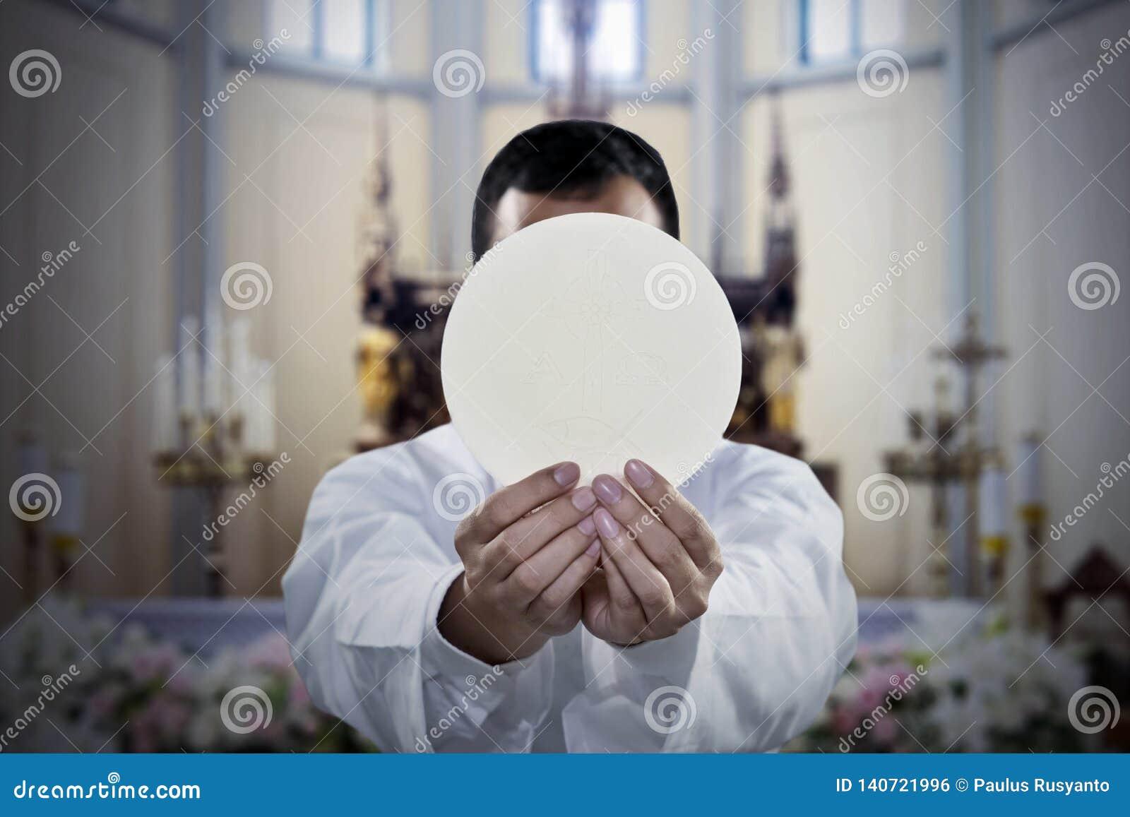 Pastor que guarda um pão sacramental na igreja
