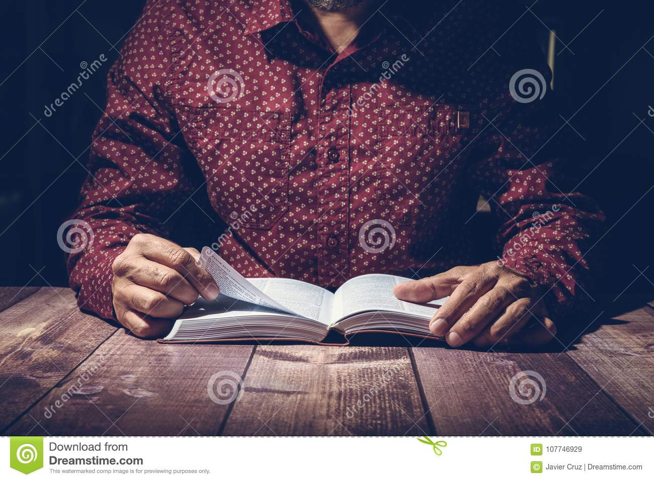 Pastor studying the Bible on a wooden desk