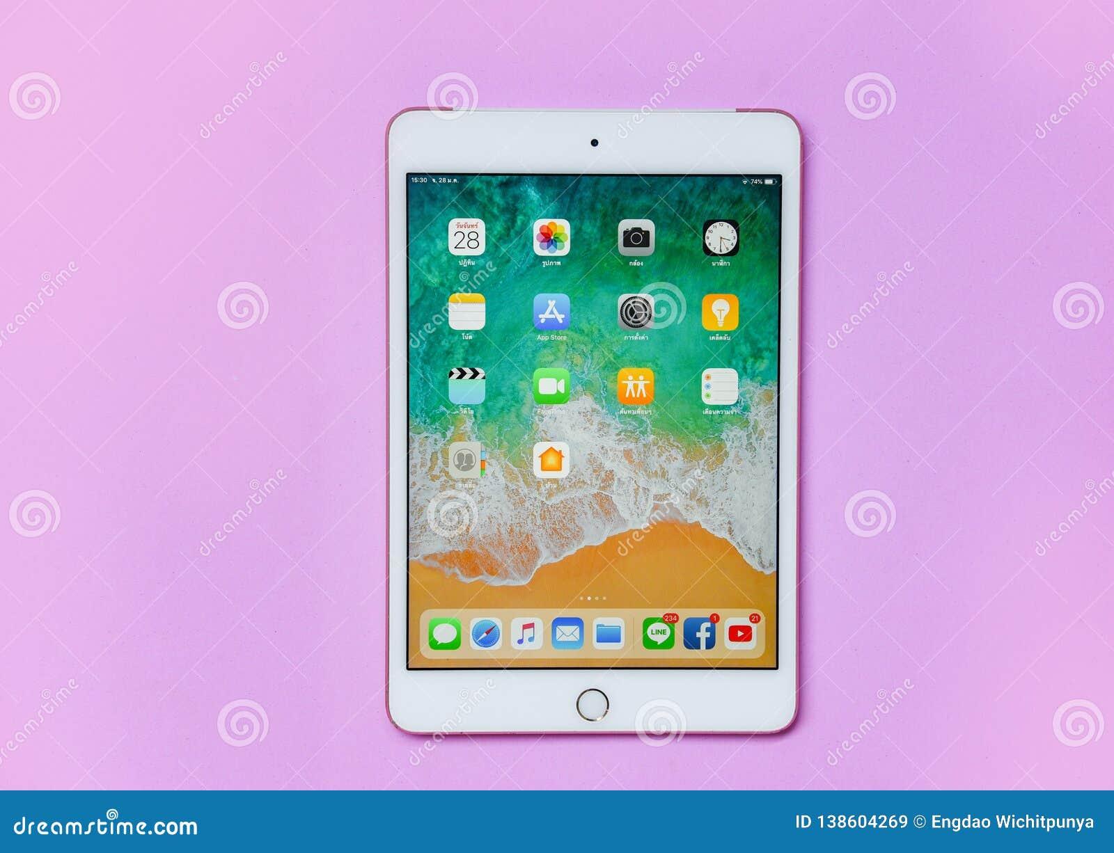 Pastylki komputerowego Nowego Jabłczanego iPad białego złota mini kolor z pokazu ekranu przodem na różowym tle