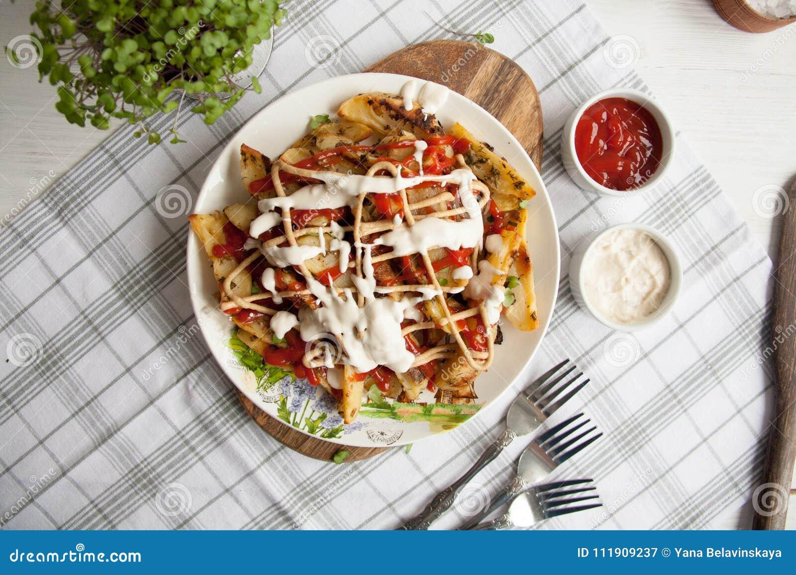 Patata al forno con i verdi, l aglio e le salse su un piatto bianco