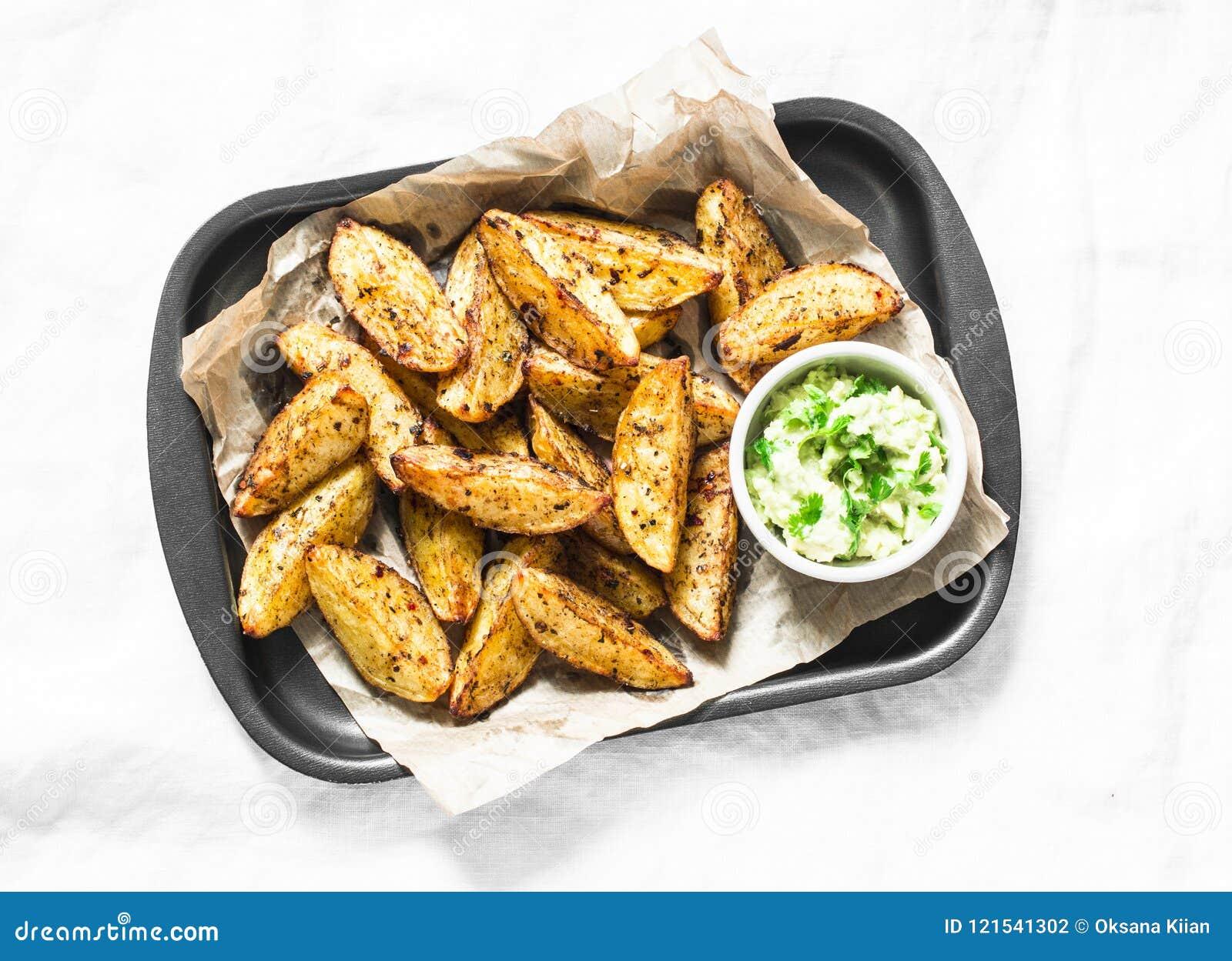 Patata al forno con la salsa dell avocado su fondo leggero, vista superiore Spuntino o aperitivi deliziosi