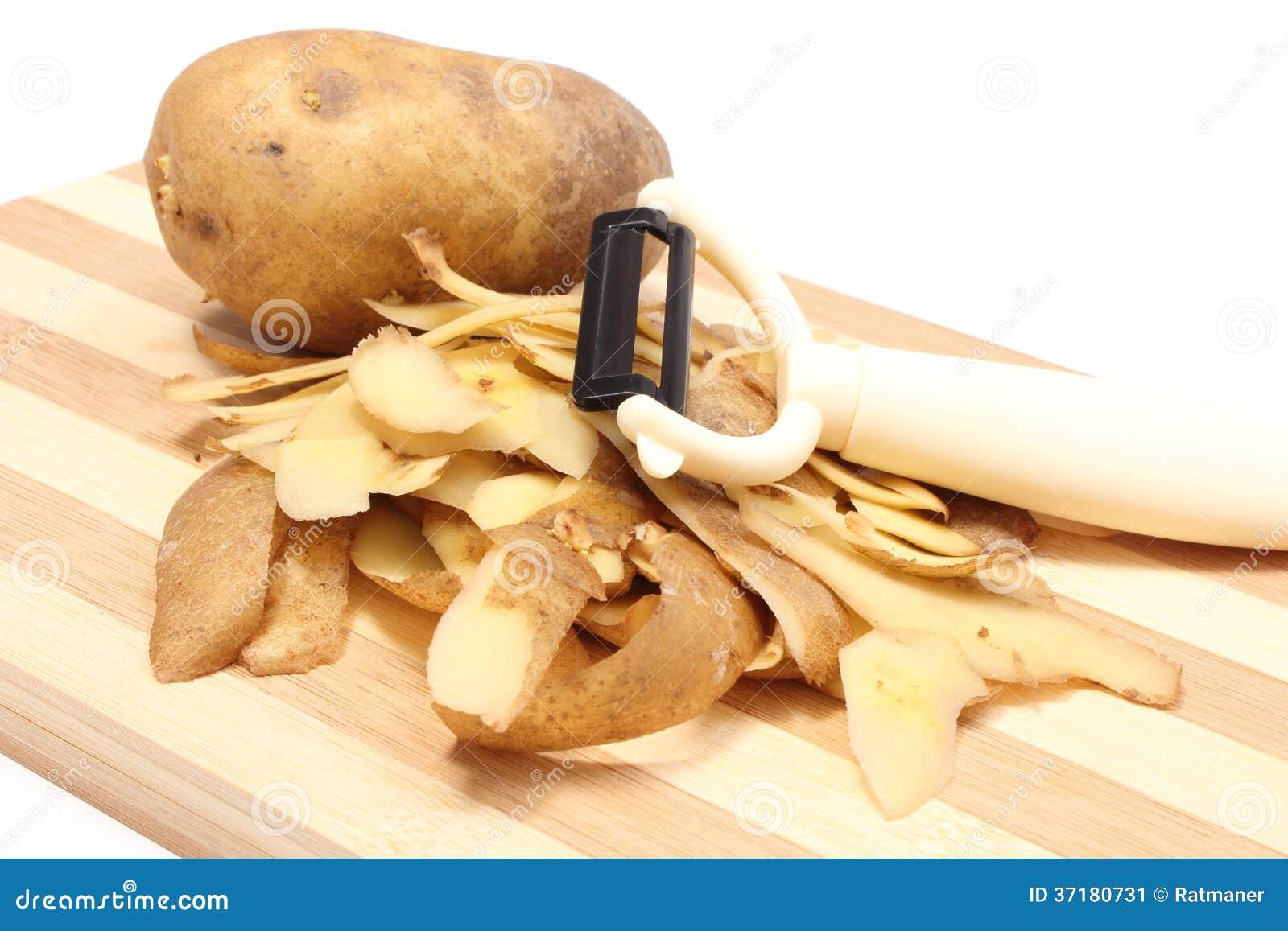 Patata con las cáscaras y policía que miente en tabla de cortar de madera