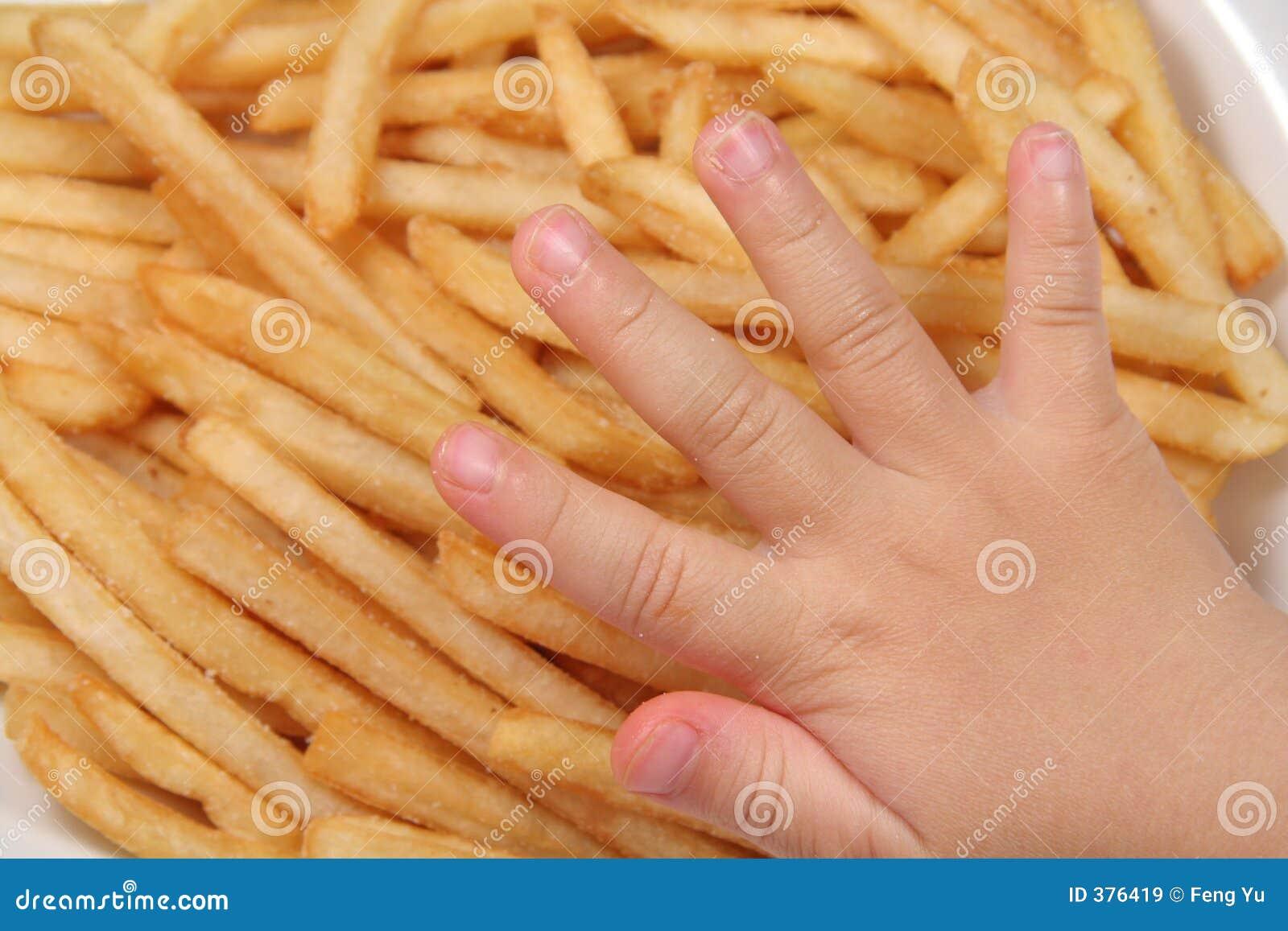 Patatas fritas y mano del niño