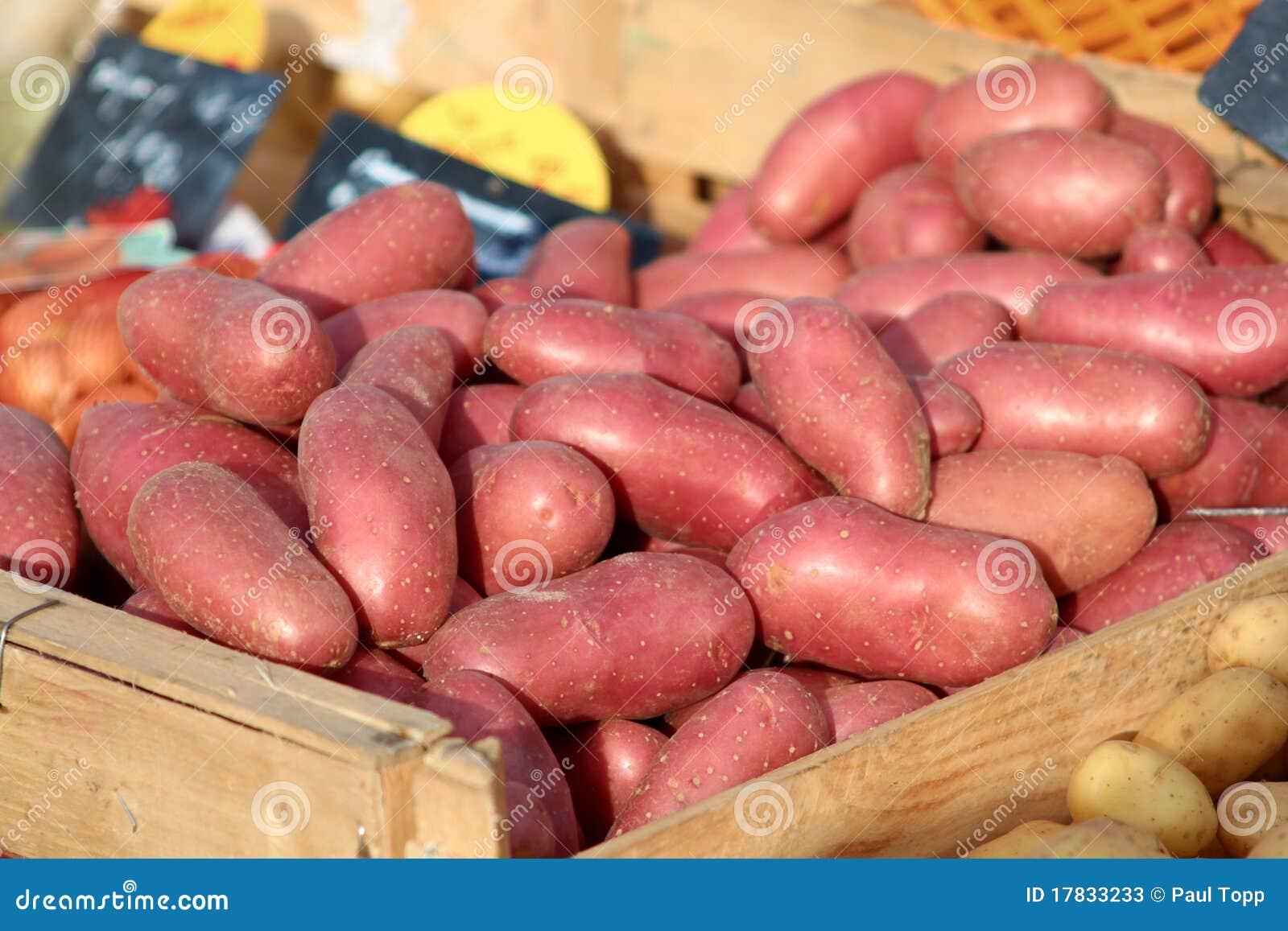 Patatas rojas orgánicas en un compartimiento en un mercado de los granjeros