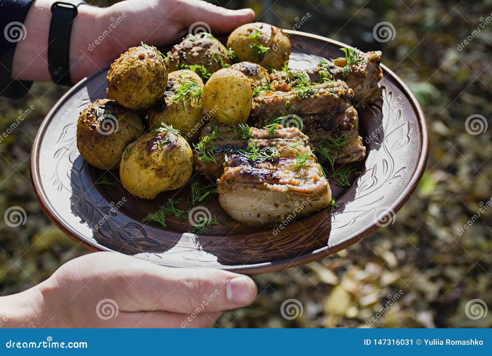 Patate cotte con le costole di carne di maiale sul fuoco presentato su un piatto dell argilla, decorato con i verdi Cena in natur