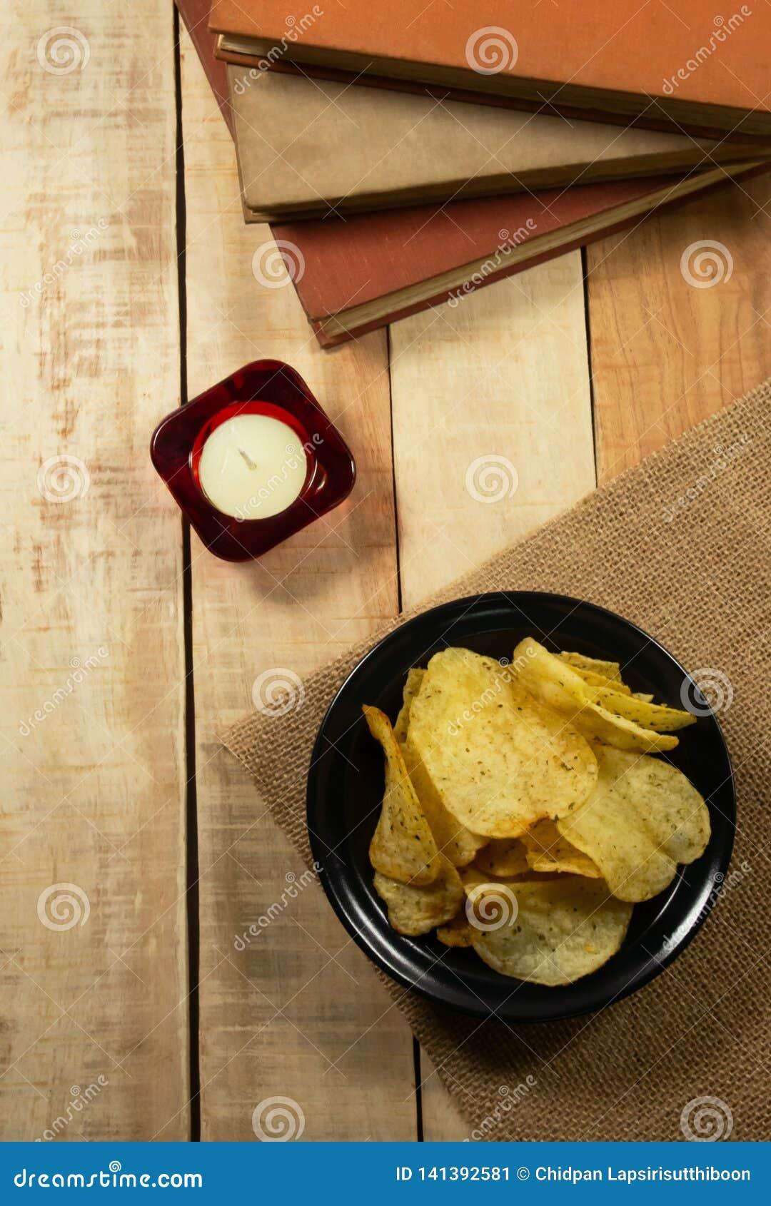 Patatine fritte in ciotola nera, candele di aromaterapia e libri su un pavimento di legno