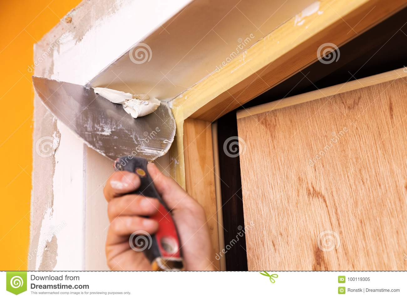 Patching plaster around a new door with spatula