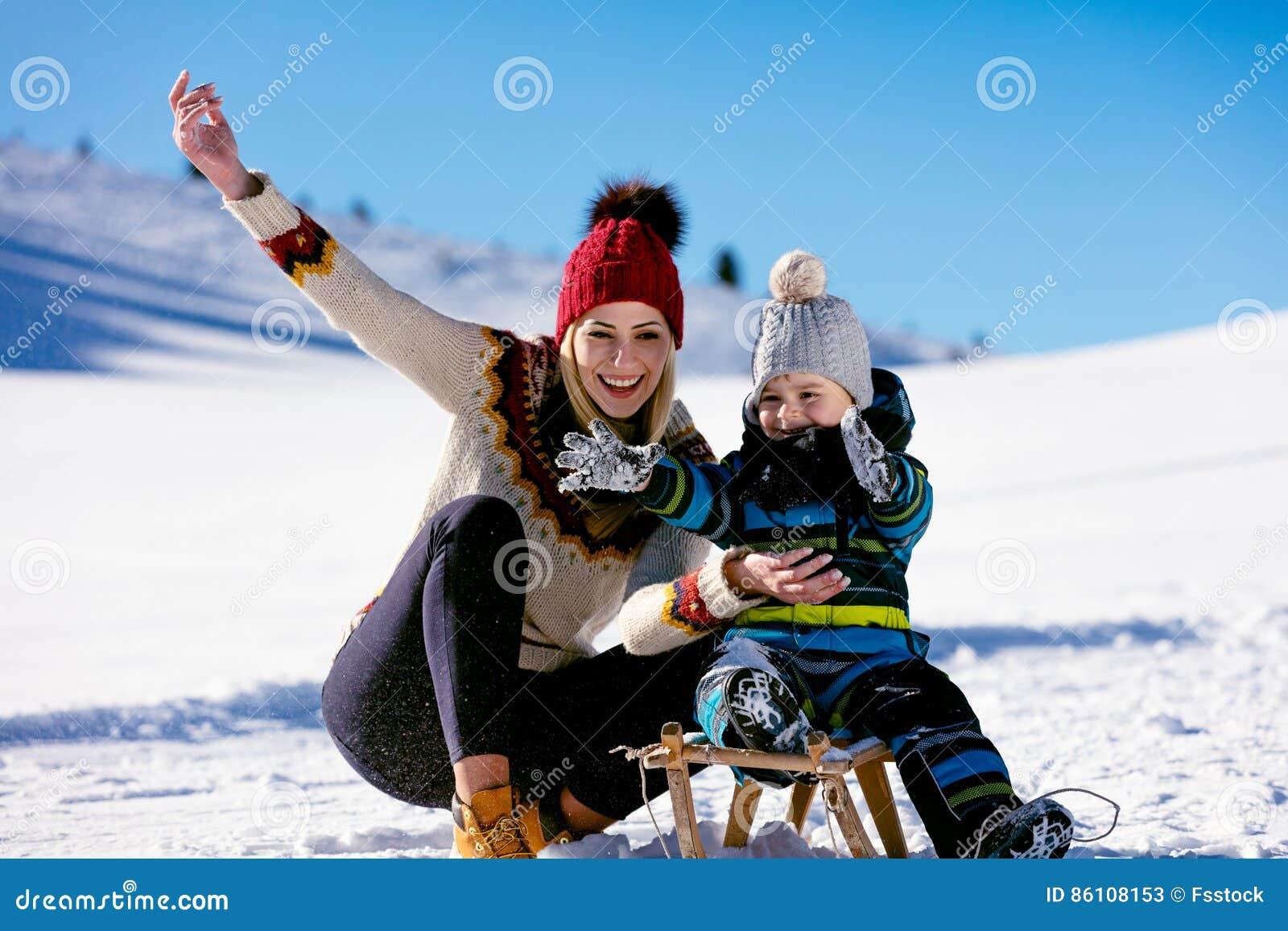 Paternidad, moda, estación y concepto de la gente - familia feliz con el niño en el trineo que camina en invierno al aire libre