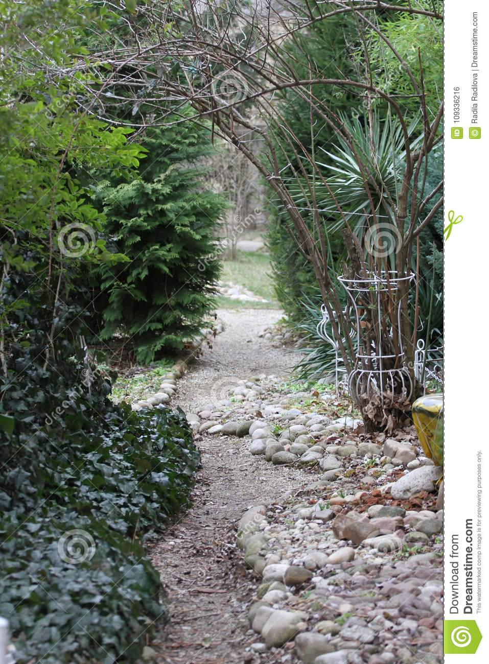 Path through the green garden. Pathway through green forest. Natural green frame with copy space. Stones pathway in garden.