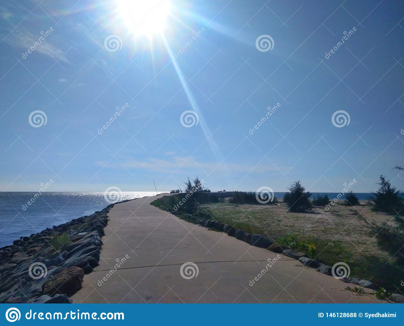 Pathway to pier and ocean view with wave breaker stone -image