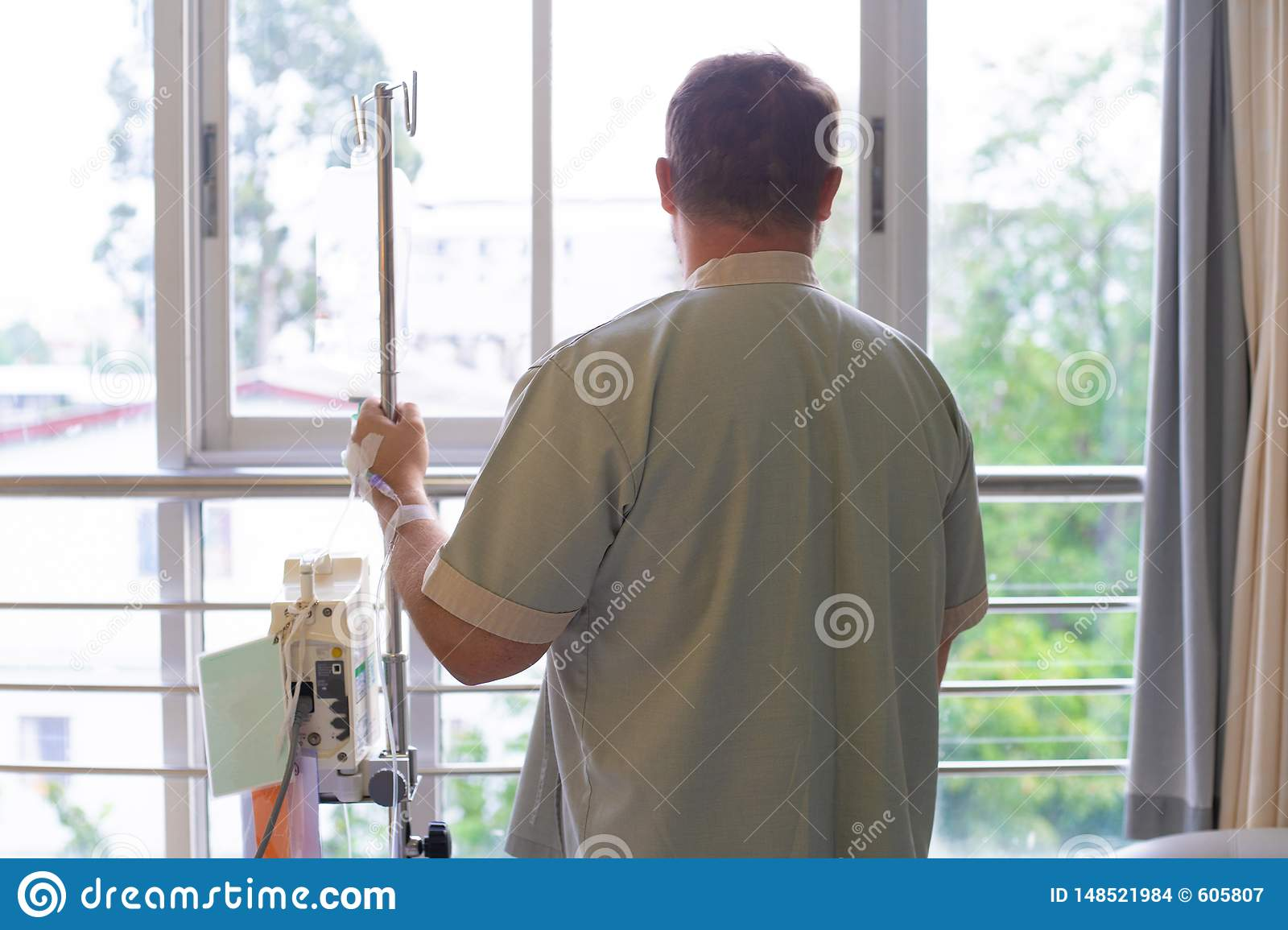 Patient with a dropper looks out the window of the hospital room and smiles. back view. Healthcare concept.