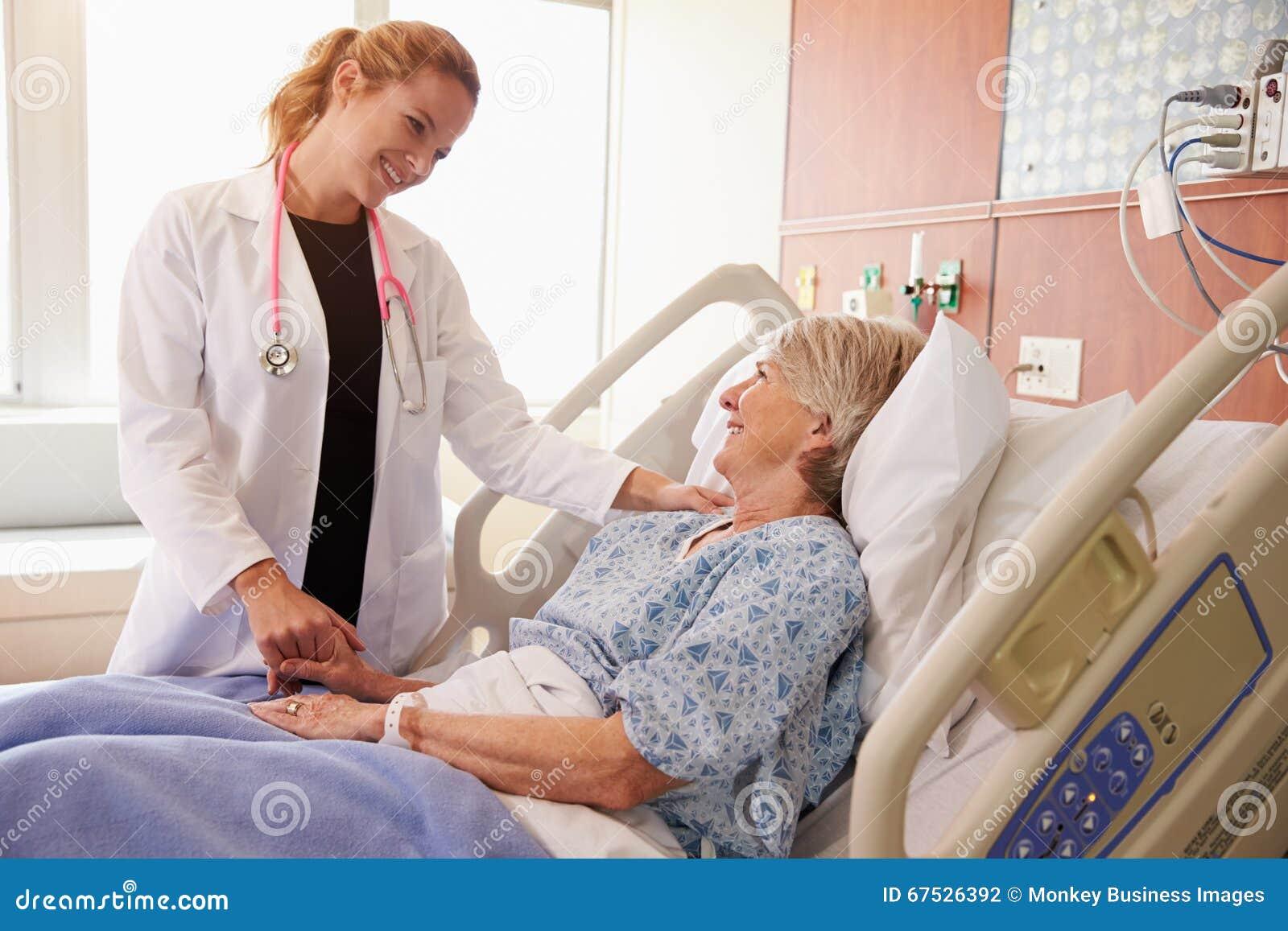 Patient féminin féminin de docteur Talks To Senior dans le lit d hôpital