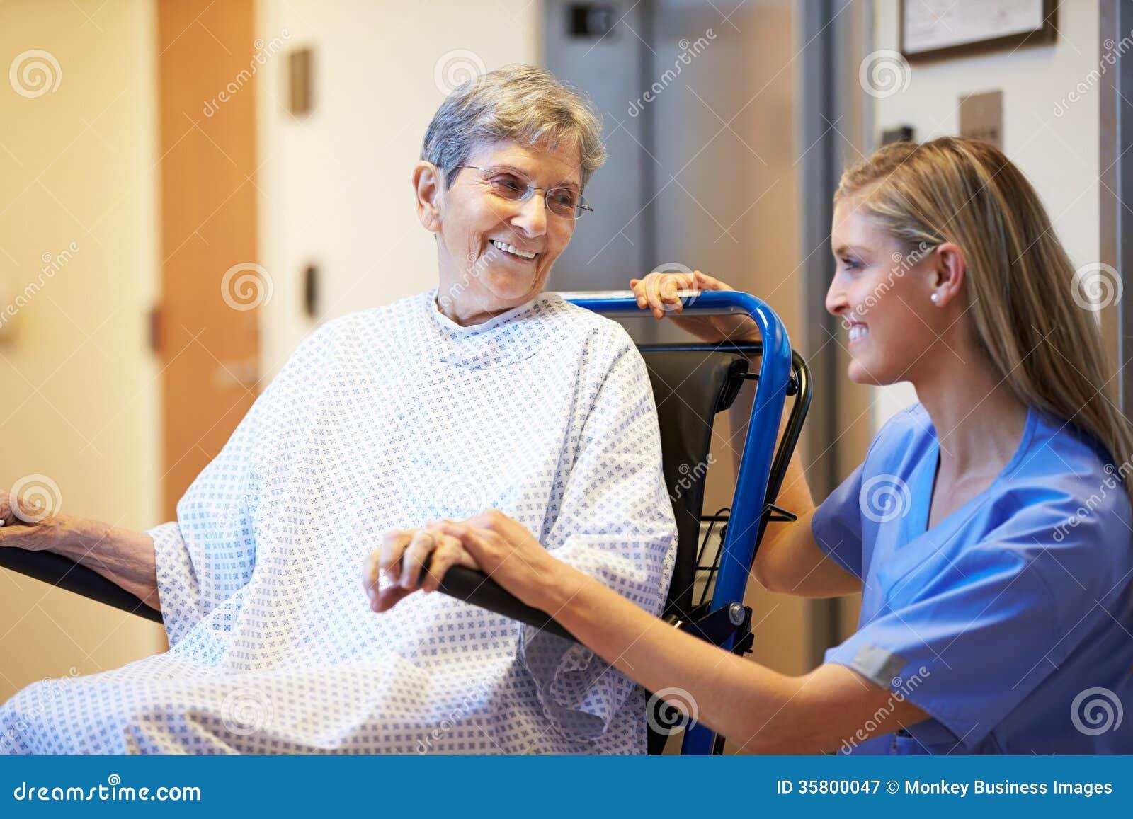 Patient féminin supérieur étant enfoncé le fauteuil roulant par l infirmière