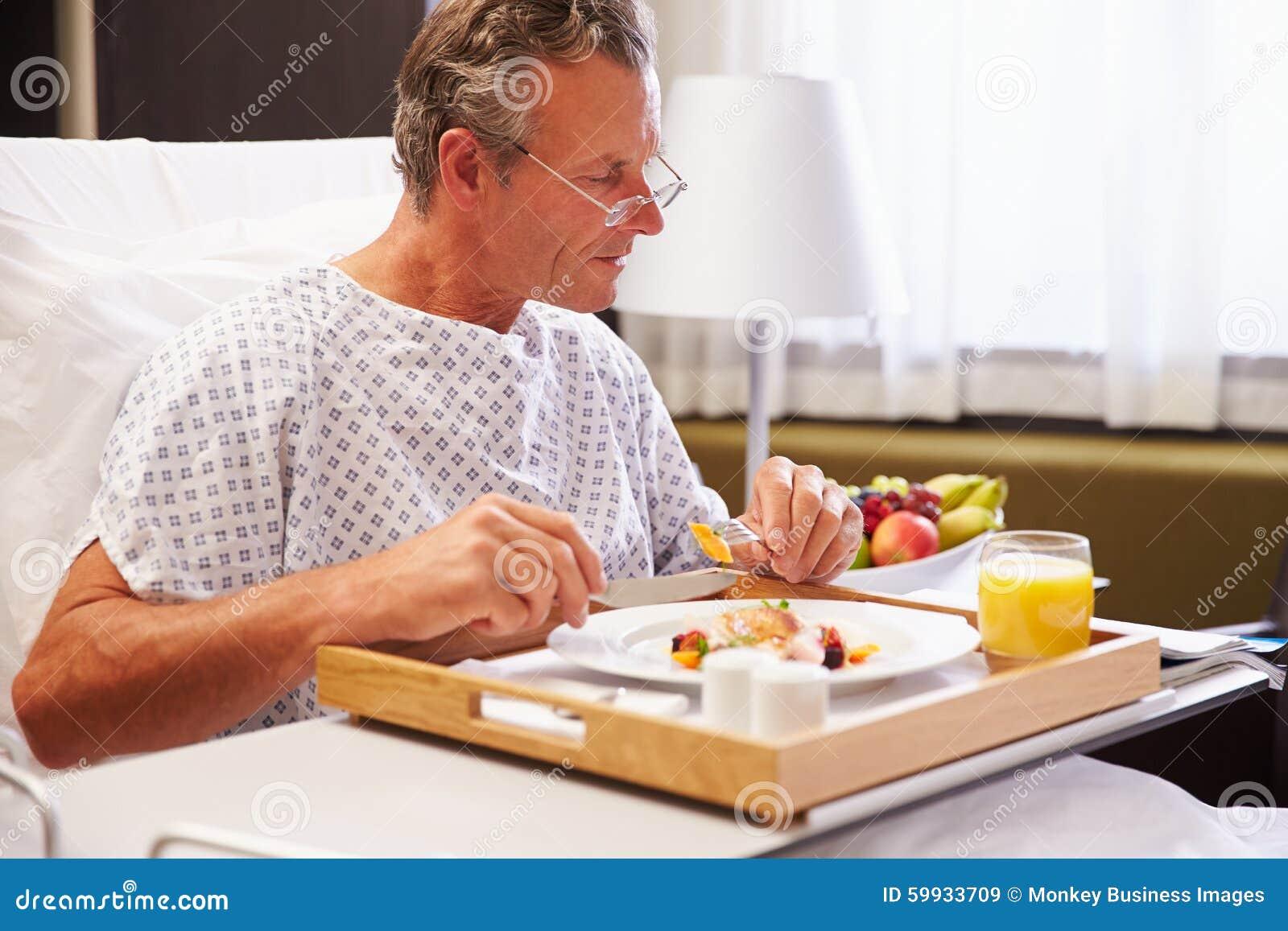 Patient masculin dans le lit d hôpital mangeant le repas du plateau