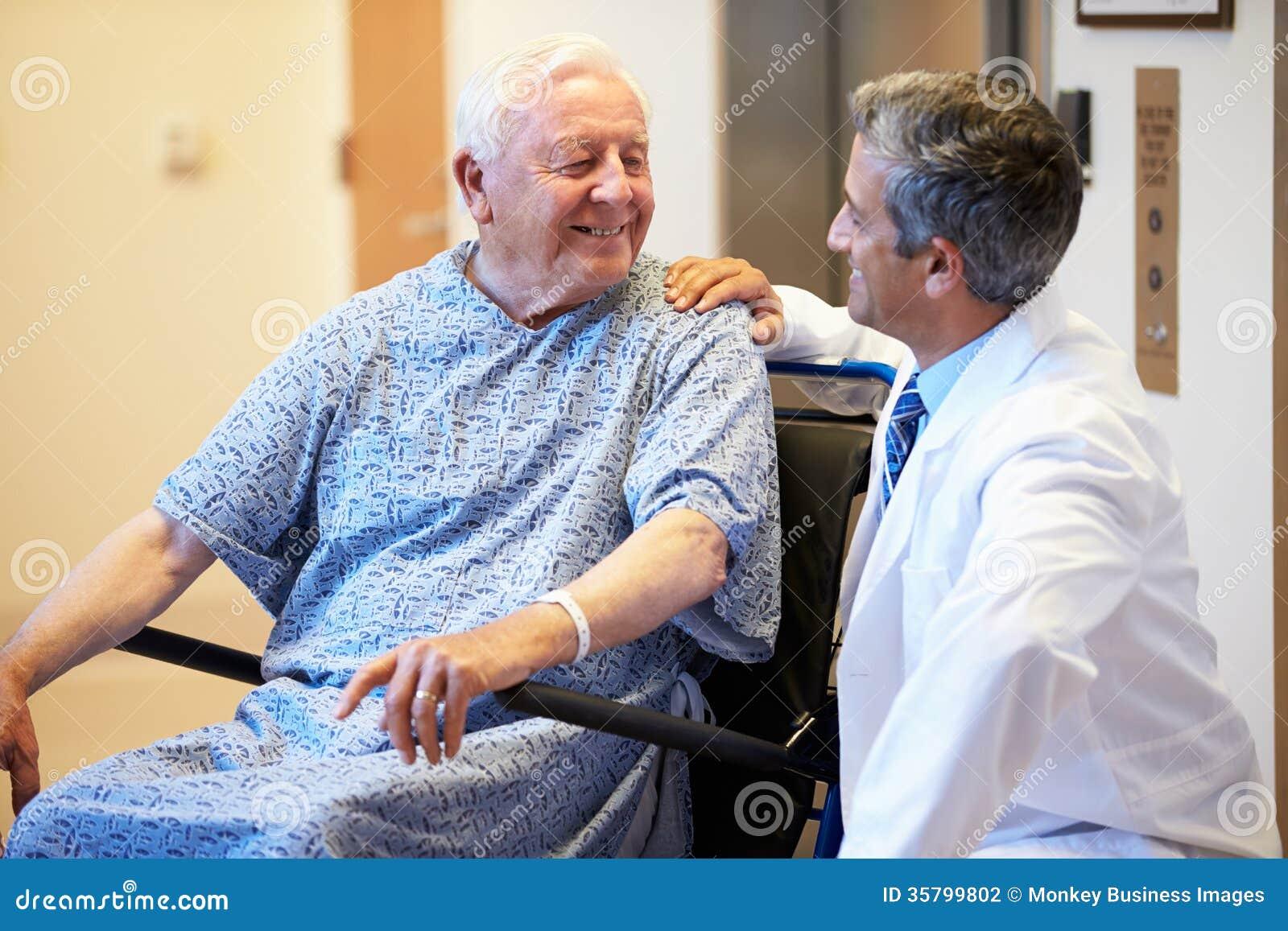 Patient masculin supérieur étant enfoncé le fauteuil roulant par le docteur