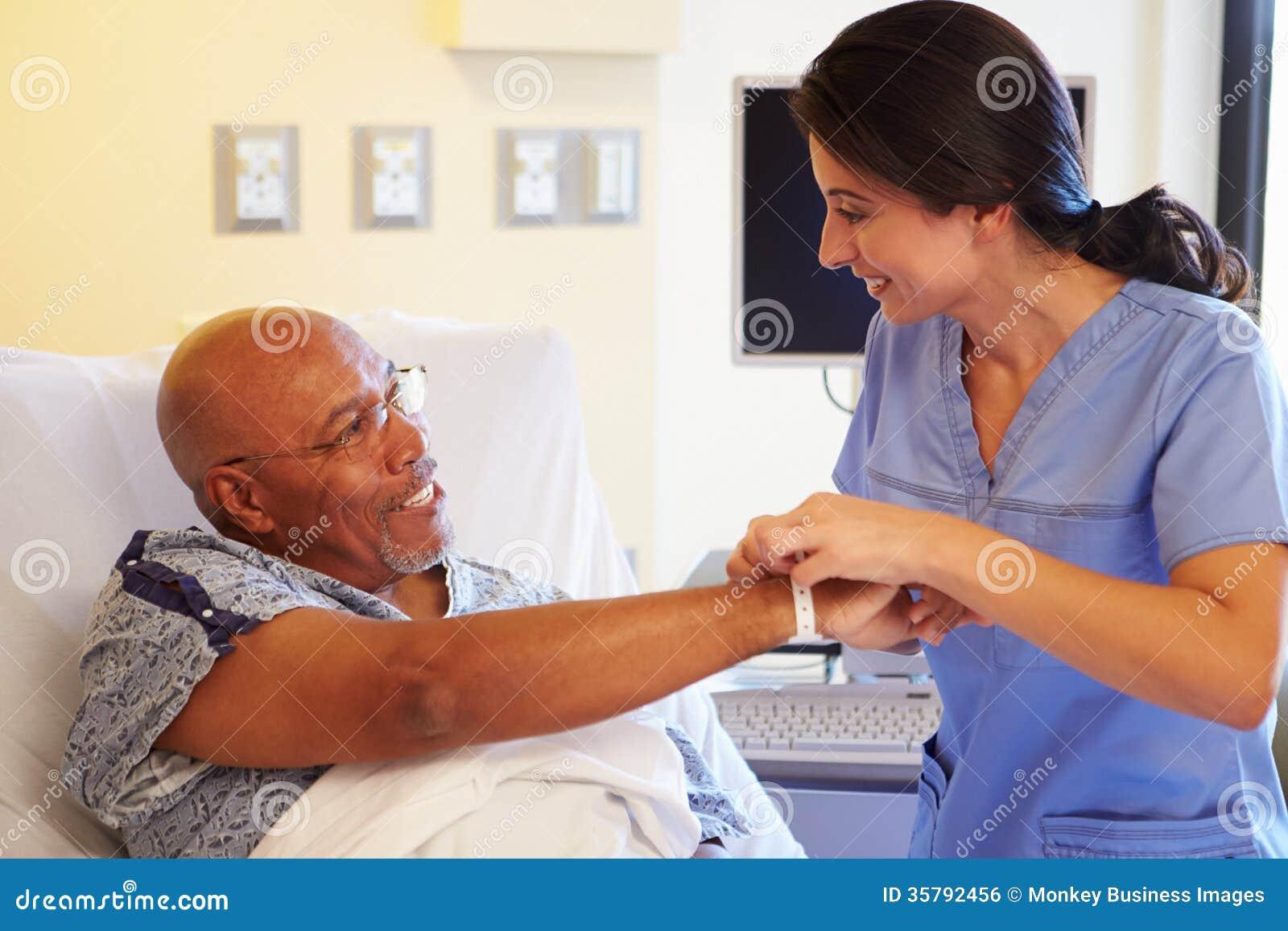 Patient masculin supérieur de Putting Wristband On d infirmière dans l hôpital