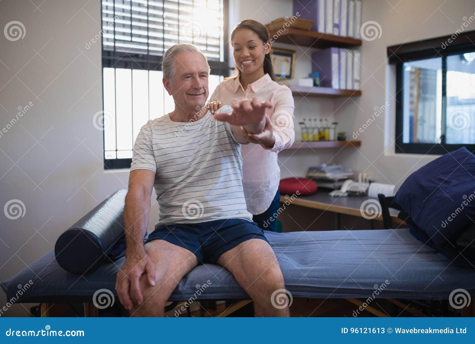 Patient masculin supérieur de sourire et docteur féminin semblant actuels