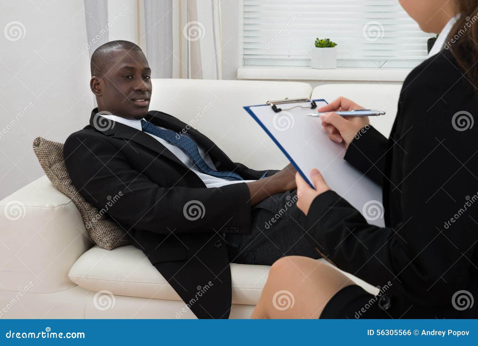 Patient på soffan och psykiatern Writing On Clipboard