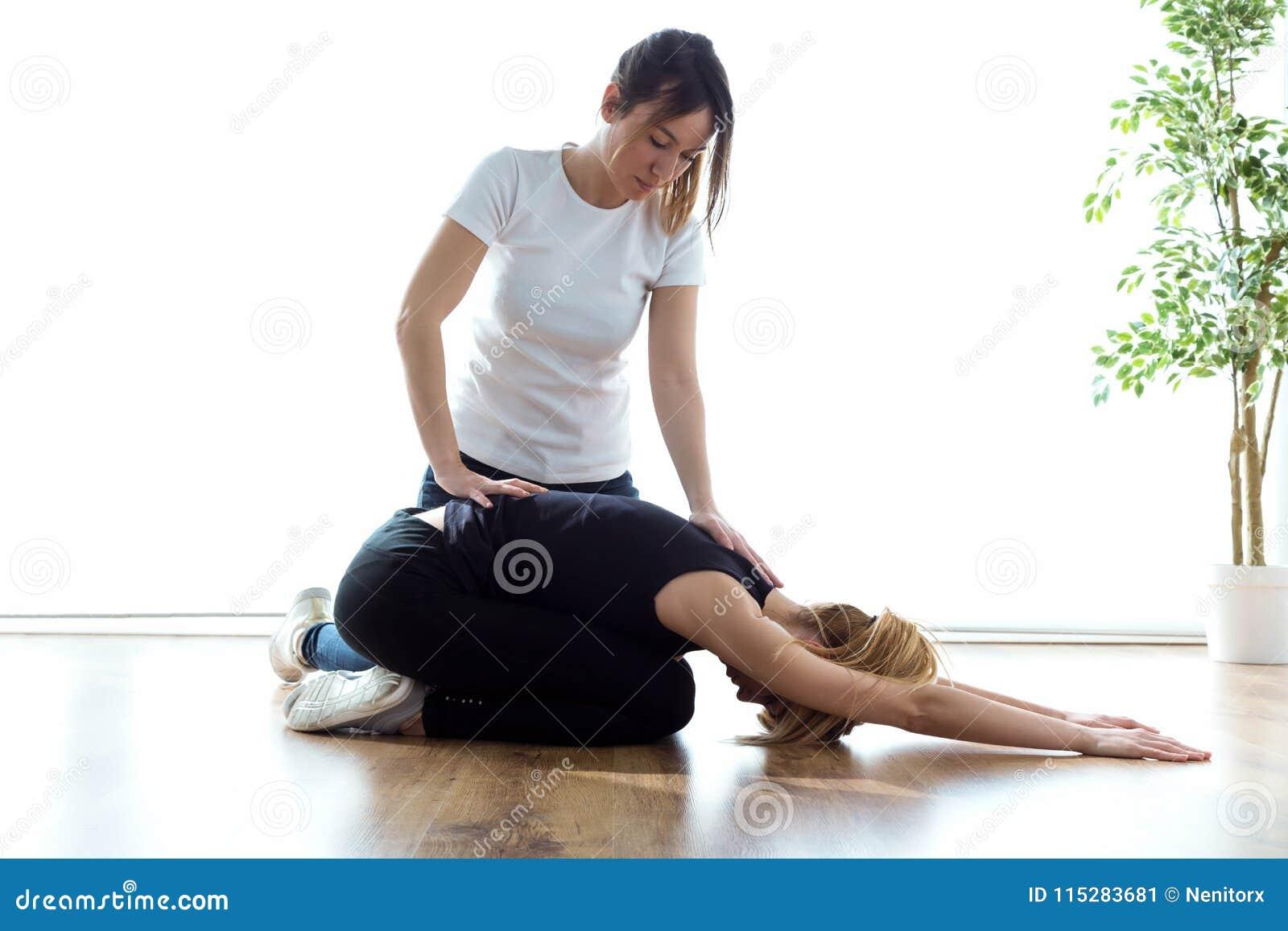 Patient som gör fysiska övningar med hans terapeut i physio rum