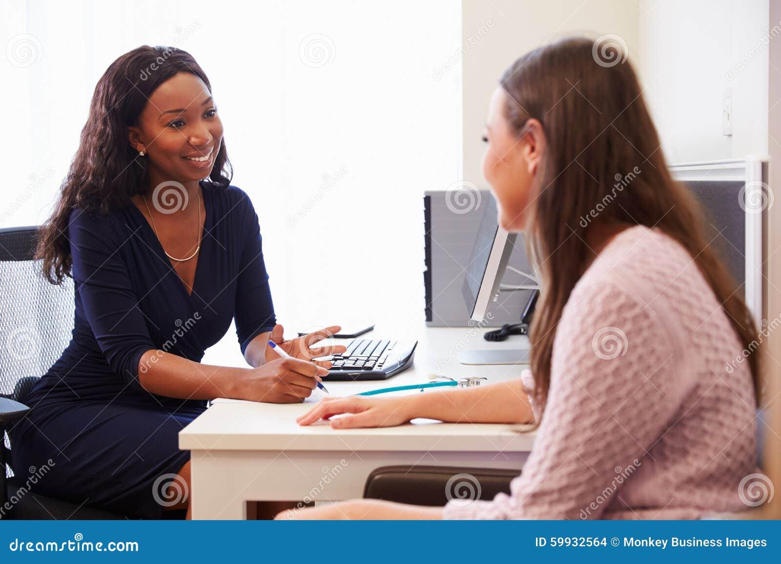 Patient som har konsultation med kvinnlig doktor In Office