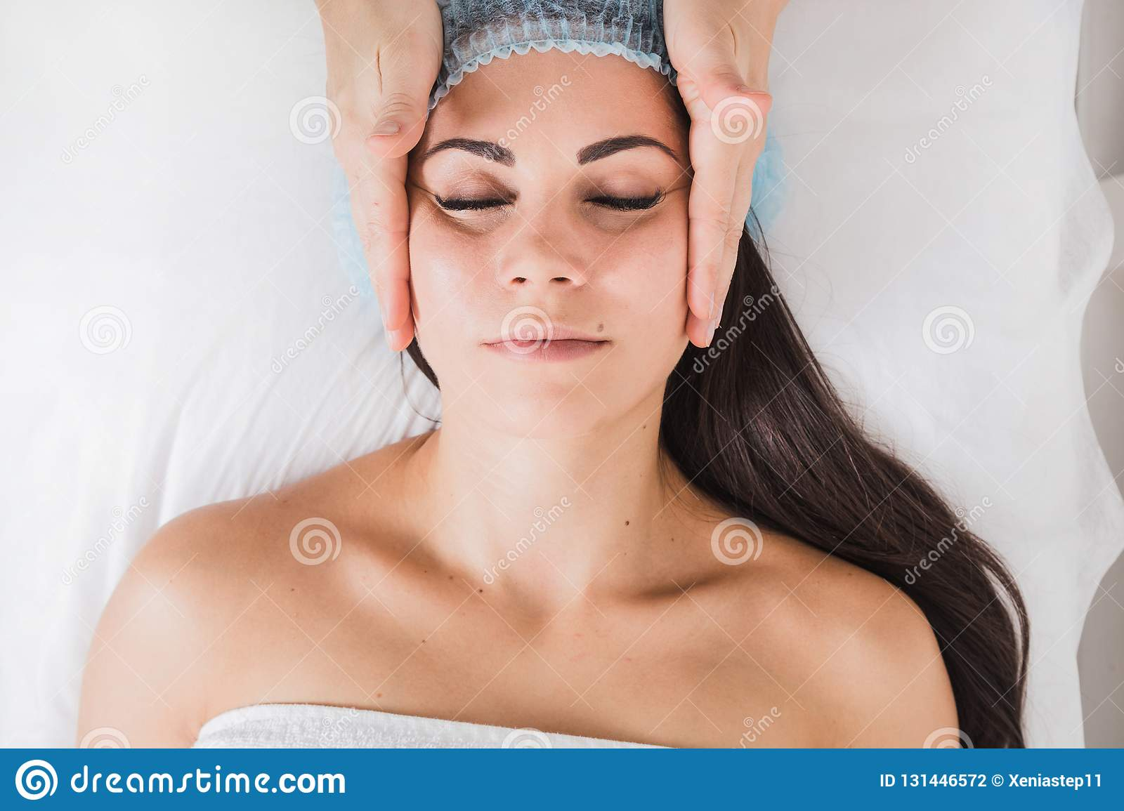Young beautiful girl getting a facial massage in a beauty salon