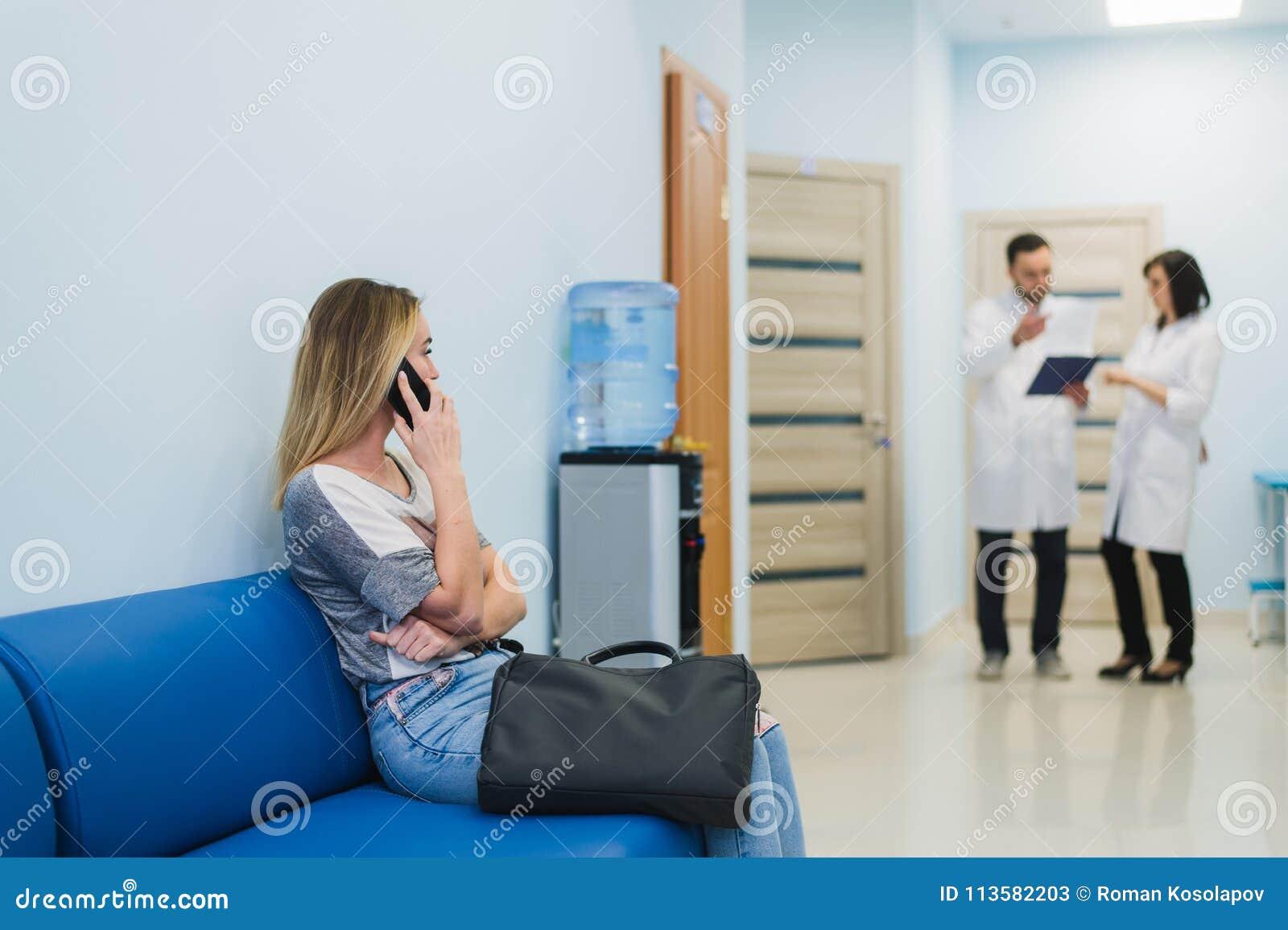 Patiente de femme en parlant au téléphone portable dans la salle d attente d hôpital
