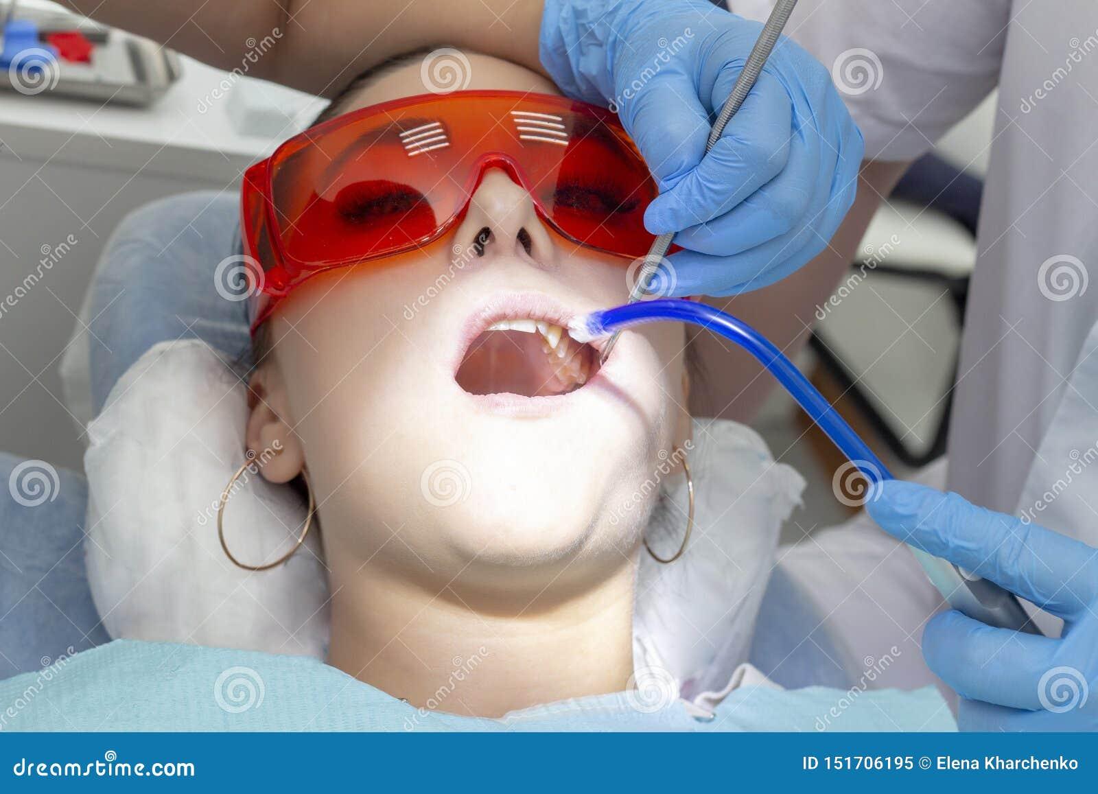 Patiente de fille à la réception au traitement de dentiste de la dent cariqueuse la fille se trouve sur la chaise dentaire avec s