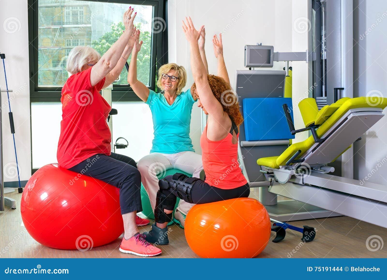 Patienten auf den Gymnastikbällen, die Übungen tun