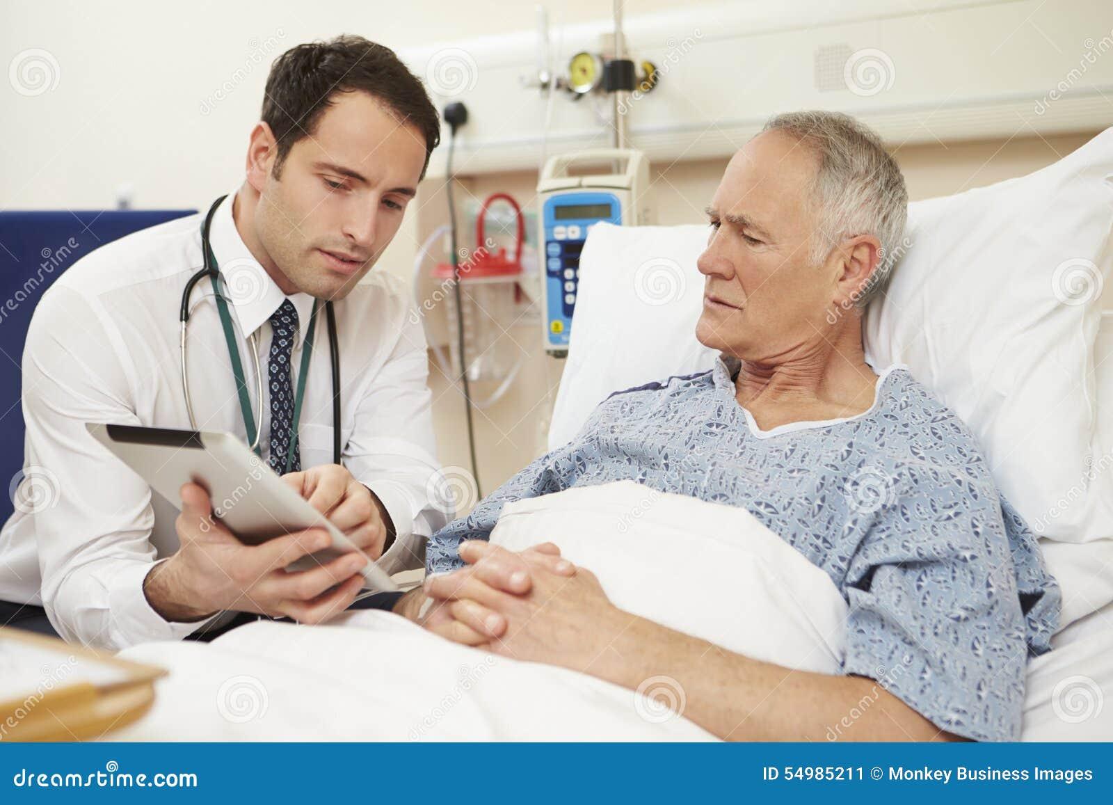 Patients för doktor Sitting By Male säng genom att använda den Digital minnestavlan