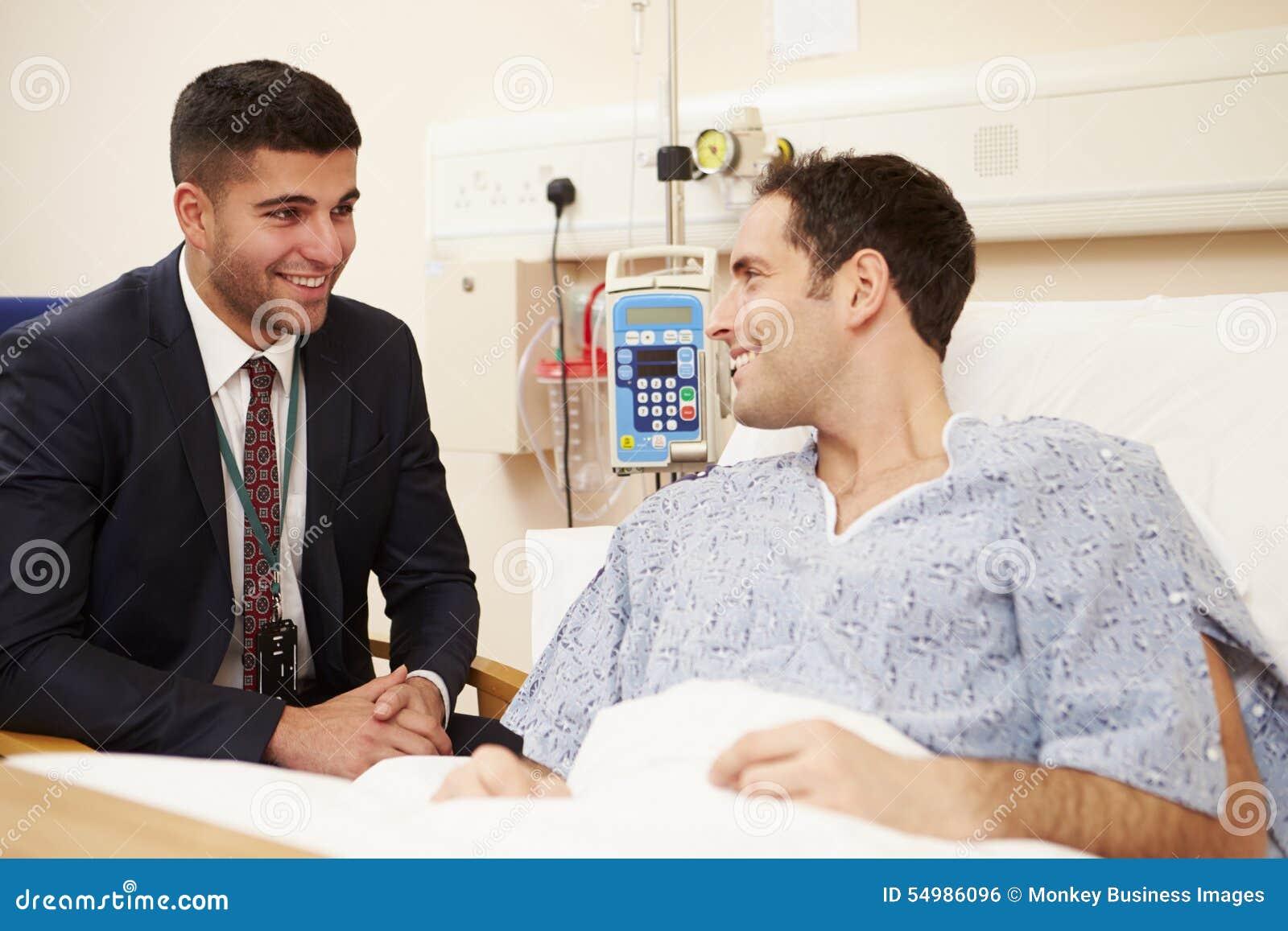 Patients för doktor Sitting By Male säng i sjukhus
