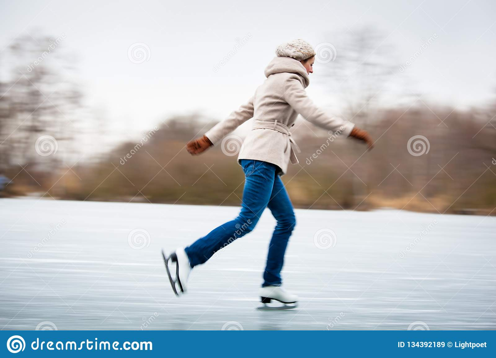 Patinage de glace de jeune femme dehors sur un étang