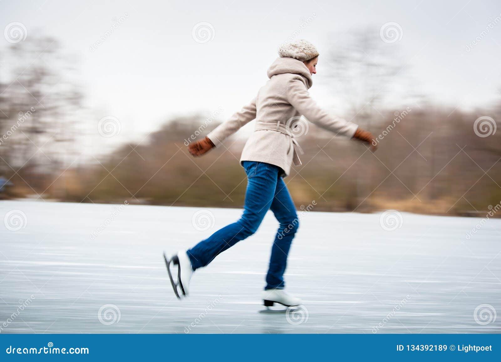 Patinagem no gelo da jovem mulher fora em uma lagoa